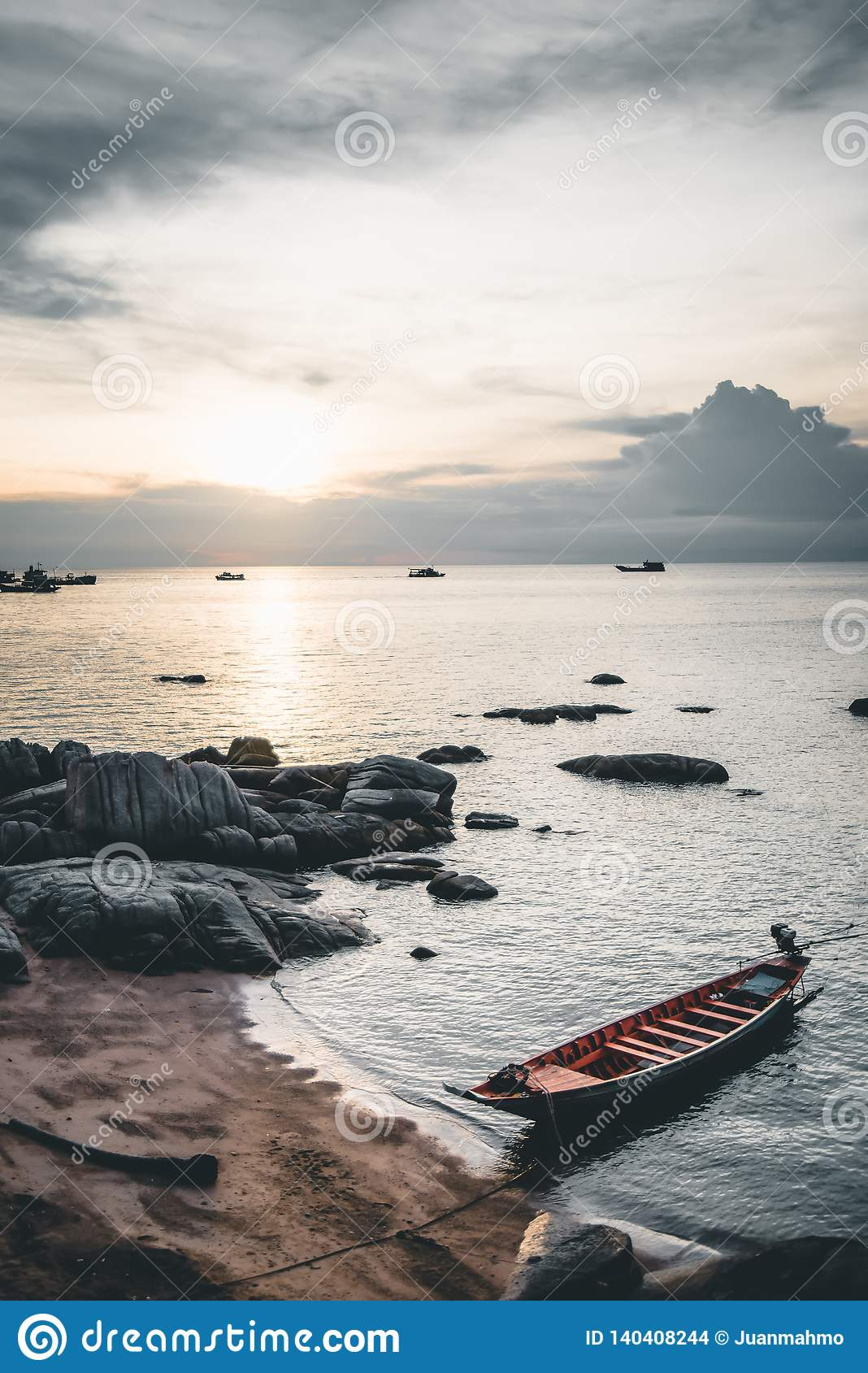Spectacular sunset on a koh-tao beach thailand with a moored boat