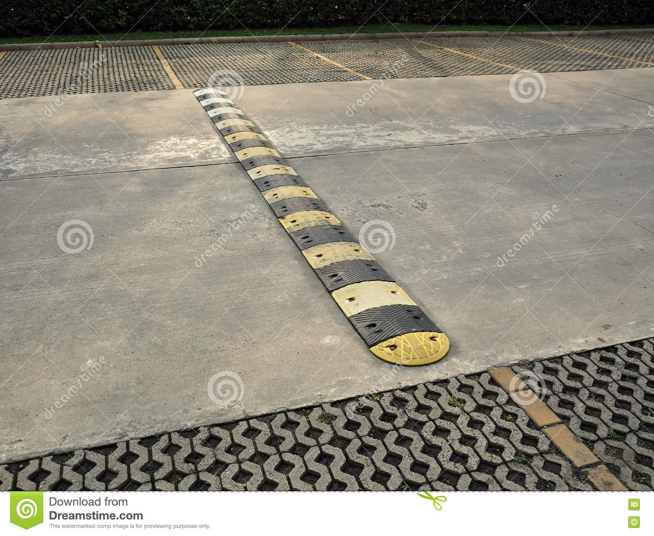 An old pale yellow and black traffic safety speed bump on a concrete road  at parking lot