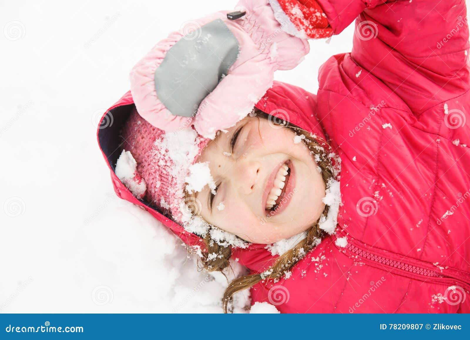 Speels meisje die met vlechten in de eerste sneeuw spelen