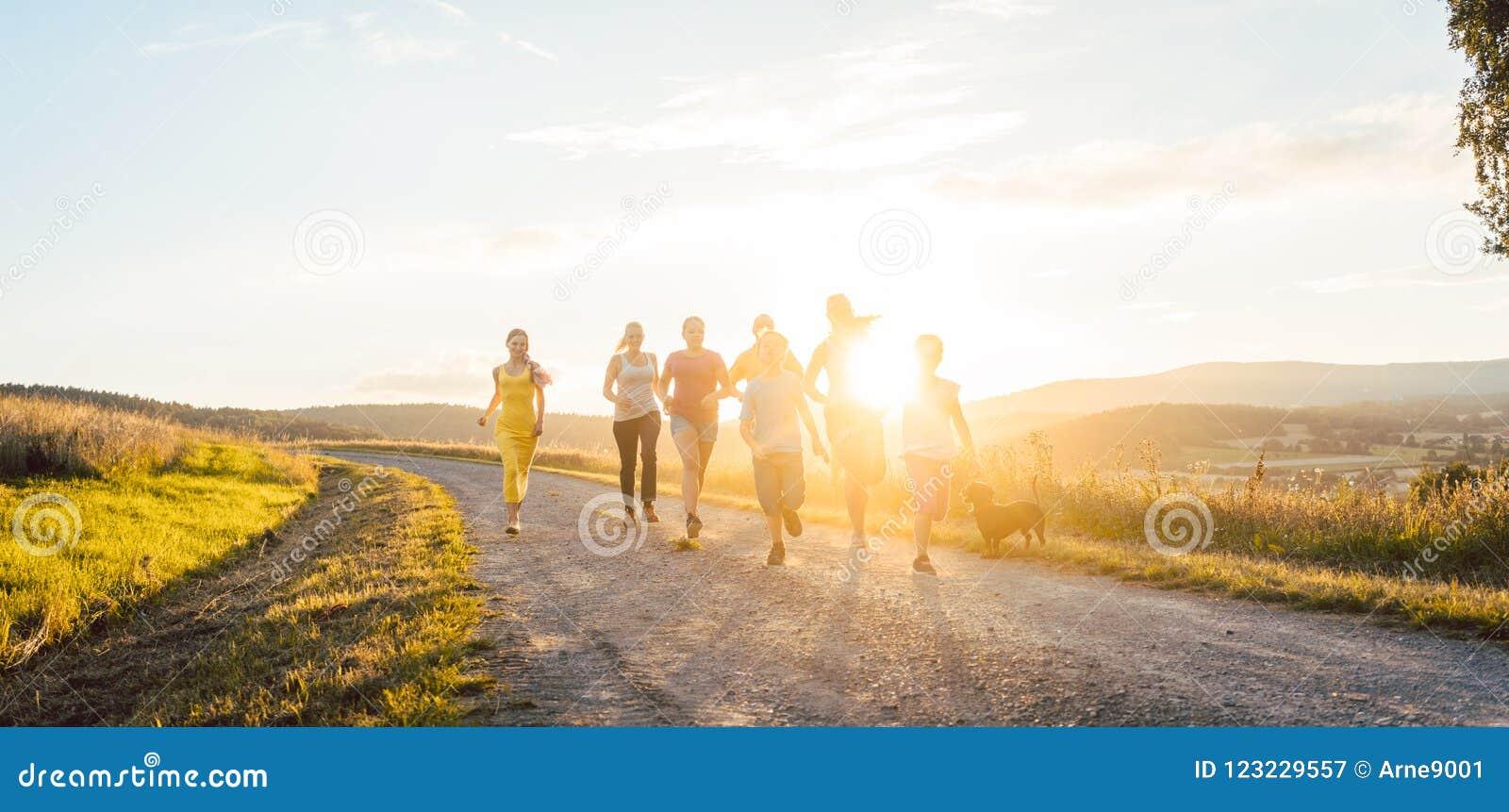 Speelse familie die en op een weg in de zomerlandschap lopen spelen