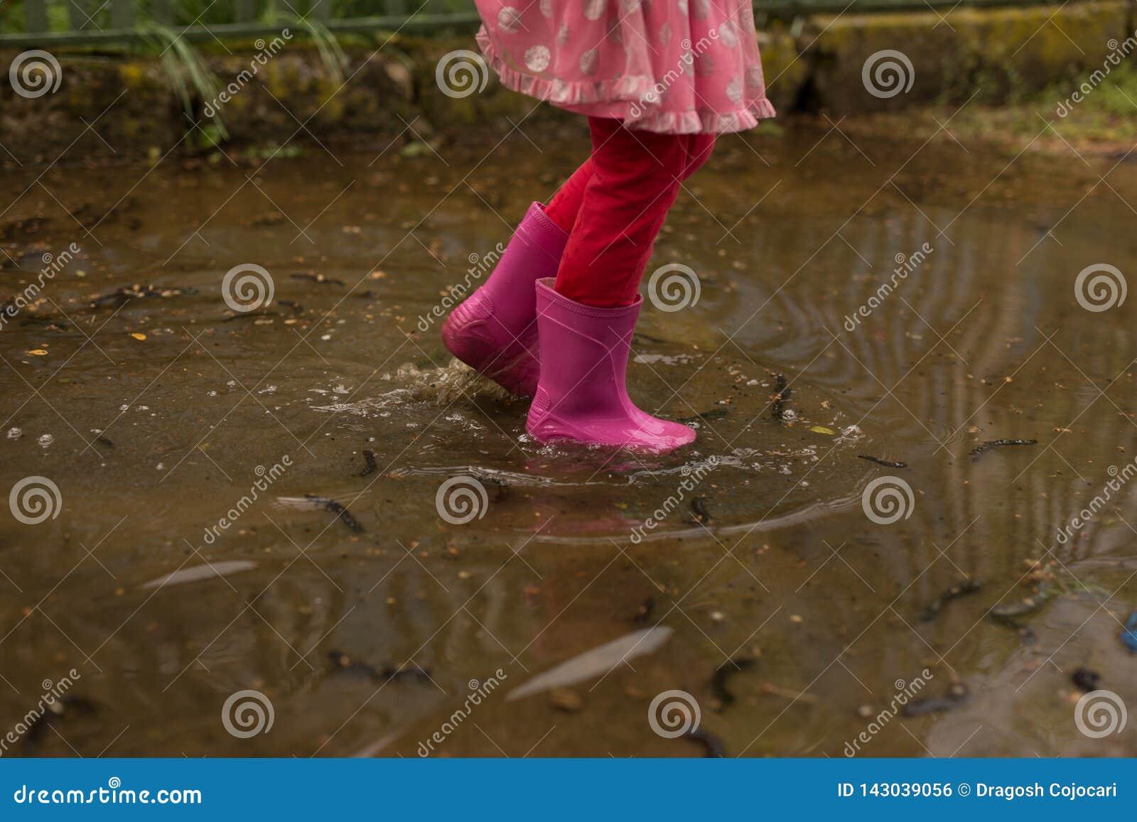 Speelse meisje openluchtsprong in vulklei in roze laars na regen Conceptueel beeld