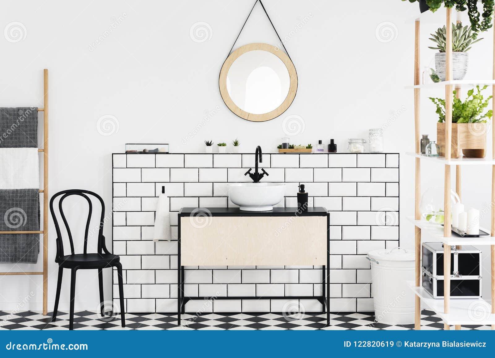 Spegel ovanför handfatet i den vita badruminre med växter och svart stol bredvid stege Verkligt foto