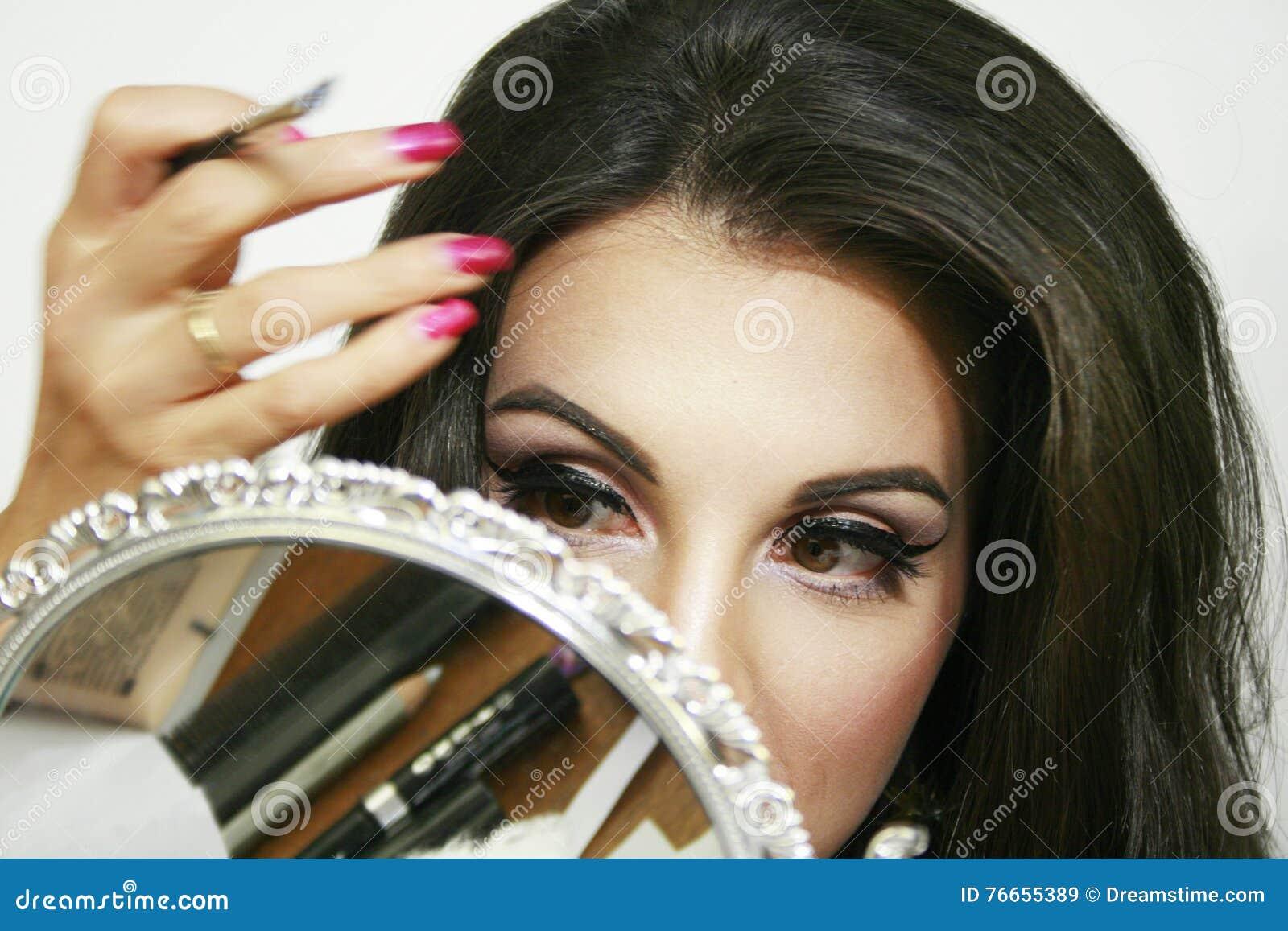 Spegeln reflekterar skönhetsmedlet, och makeupmaterial, den härliga flickan gör hennes makeup, handrörelse, rosa ögonskugga och t