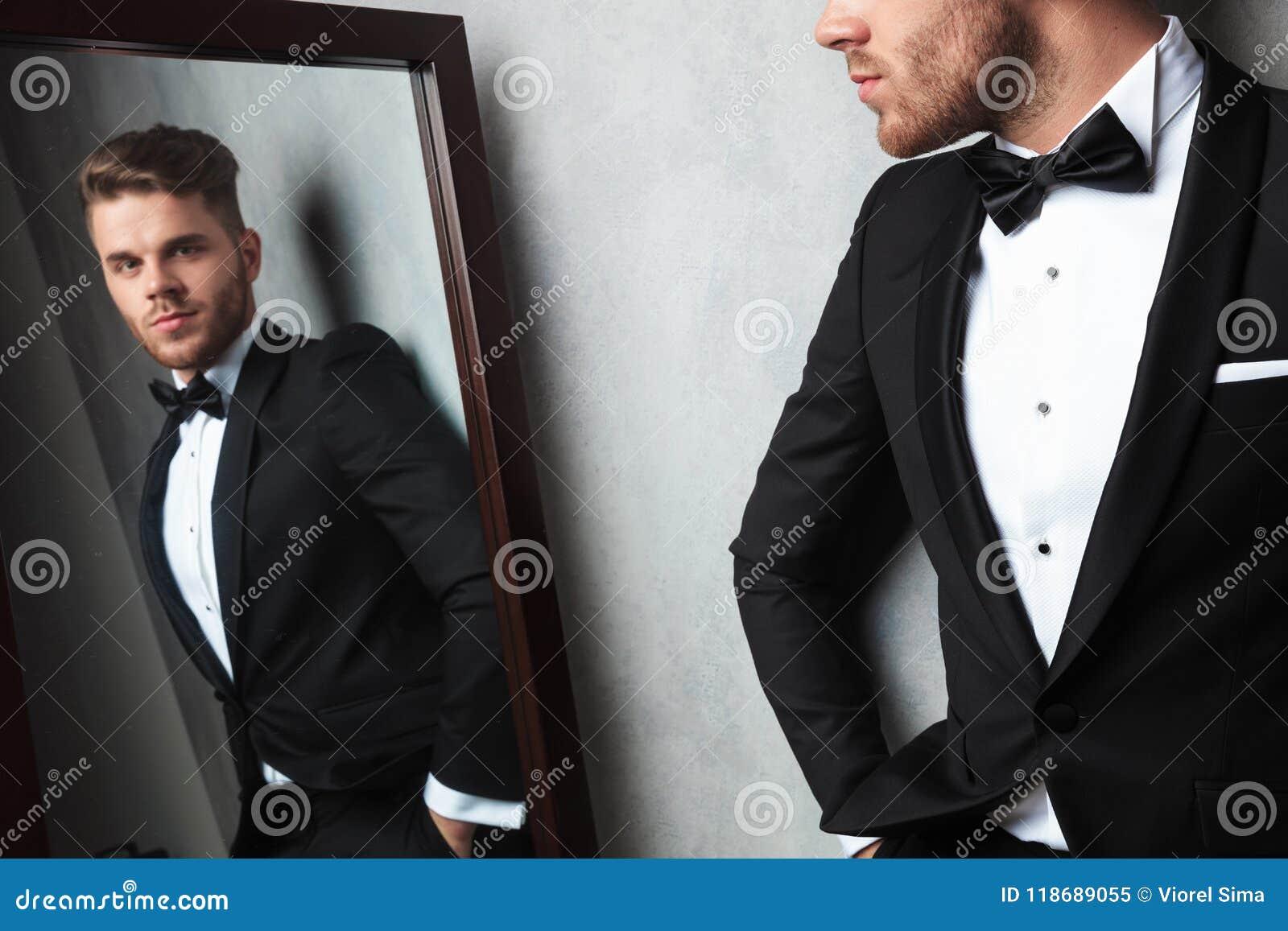 Spegelreflexion av den avkopplade unga mannen som bär en svart smoking