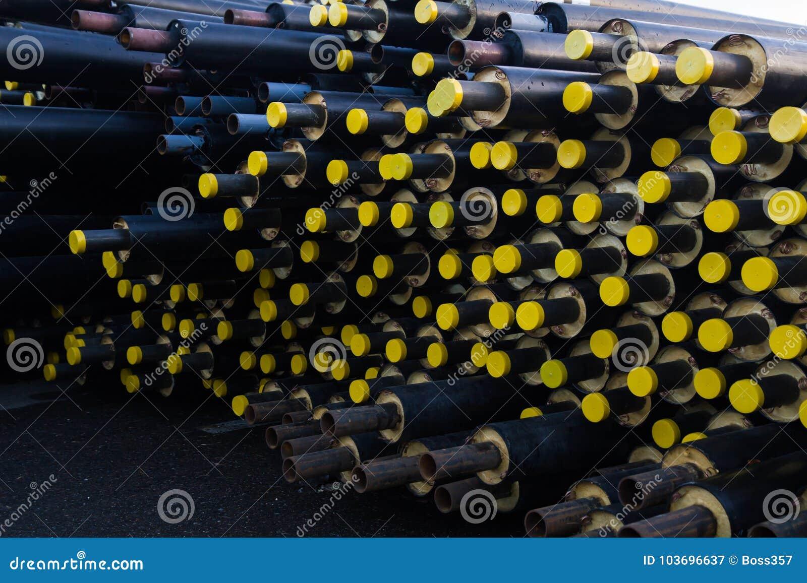 Speicherte viel schwarzes Stahlrohr mit Wärmedämmung auf Baustelle in einer Kunststoffrohrverpackung, die mit gelben Deckelrohren