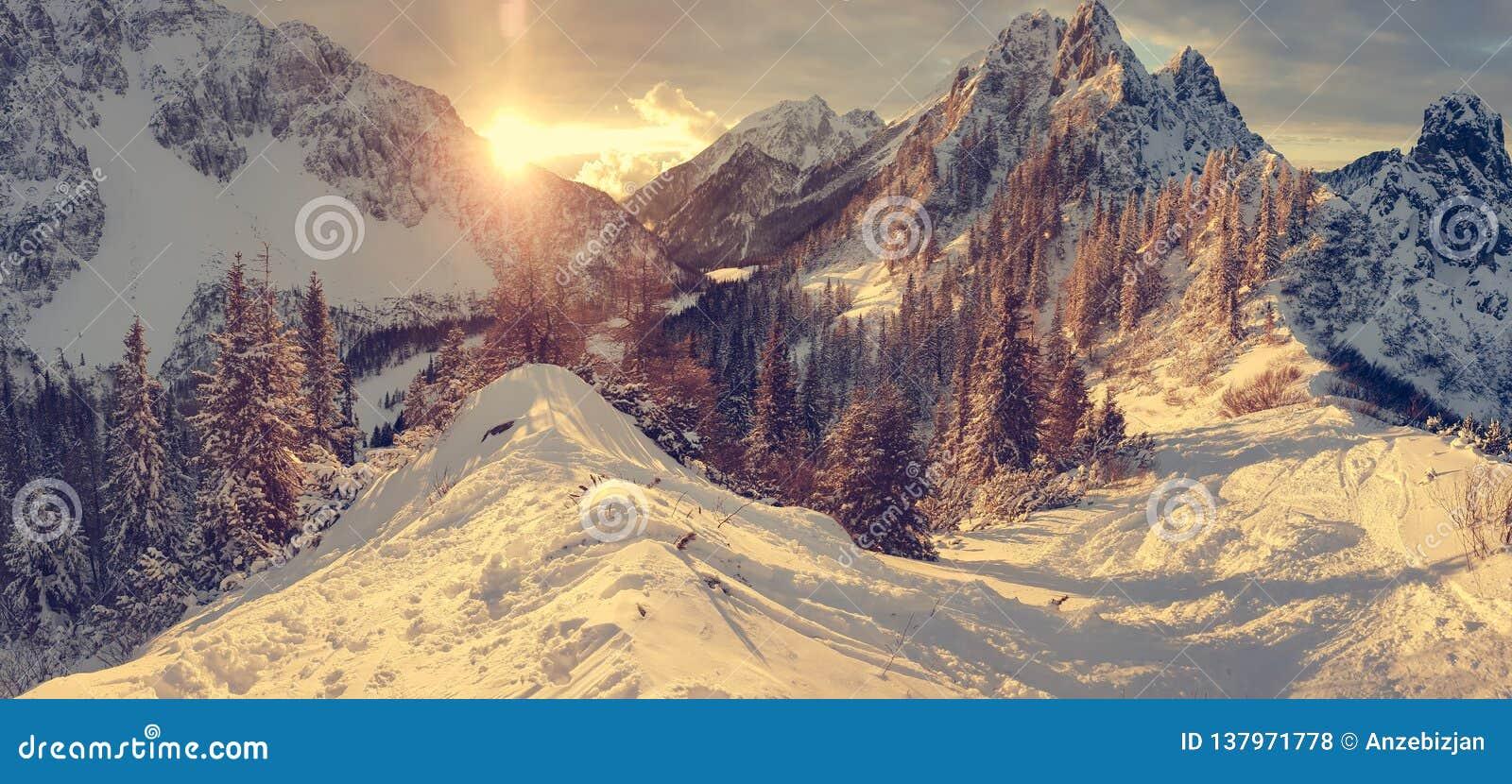 Spektakulärt vinterberglandskap exponerat av inställningssolen