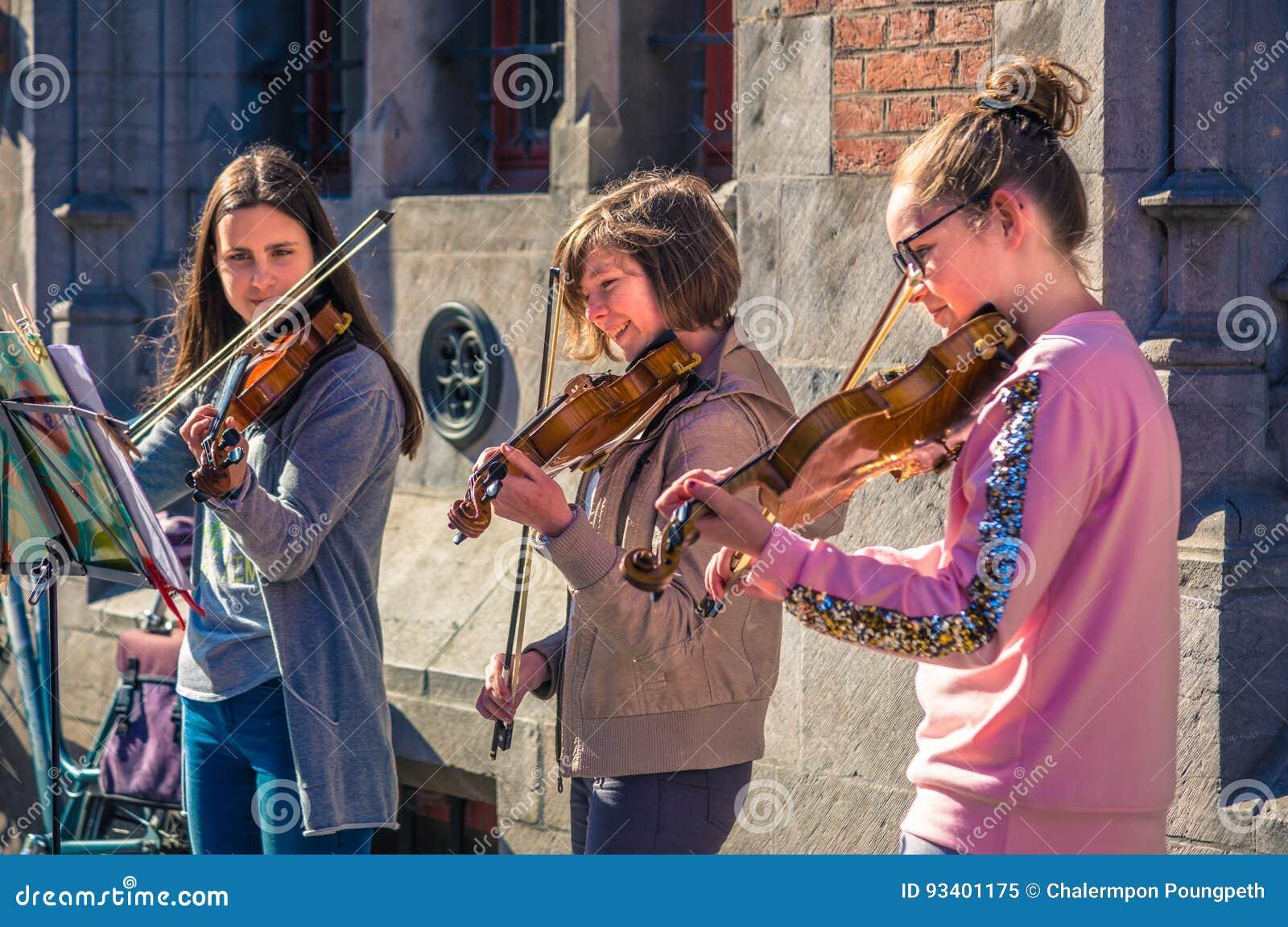 Spel van drie het gelukkige vrouwelijke tienerviolisten voor schenking