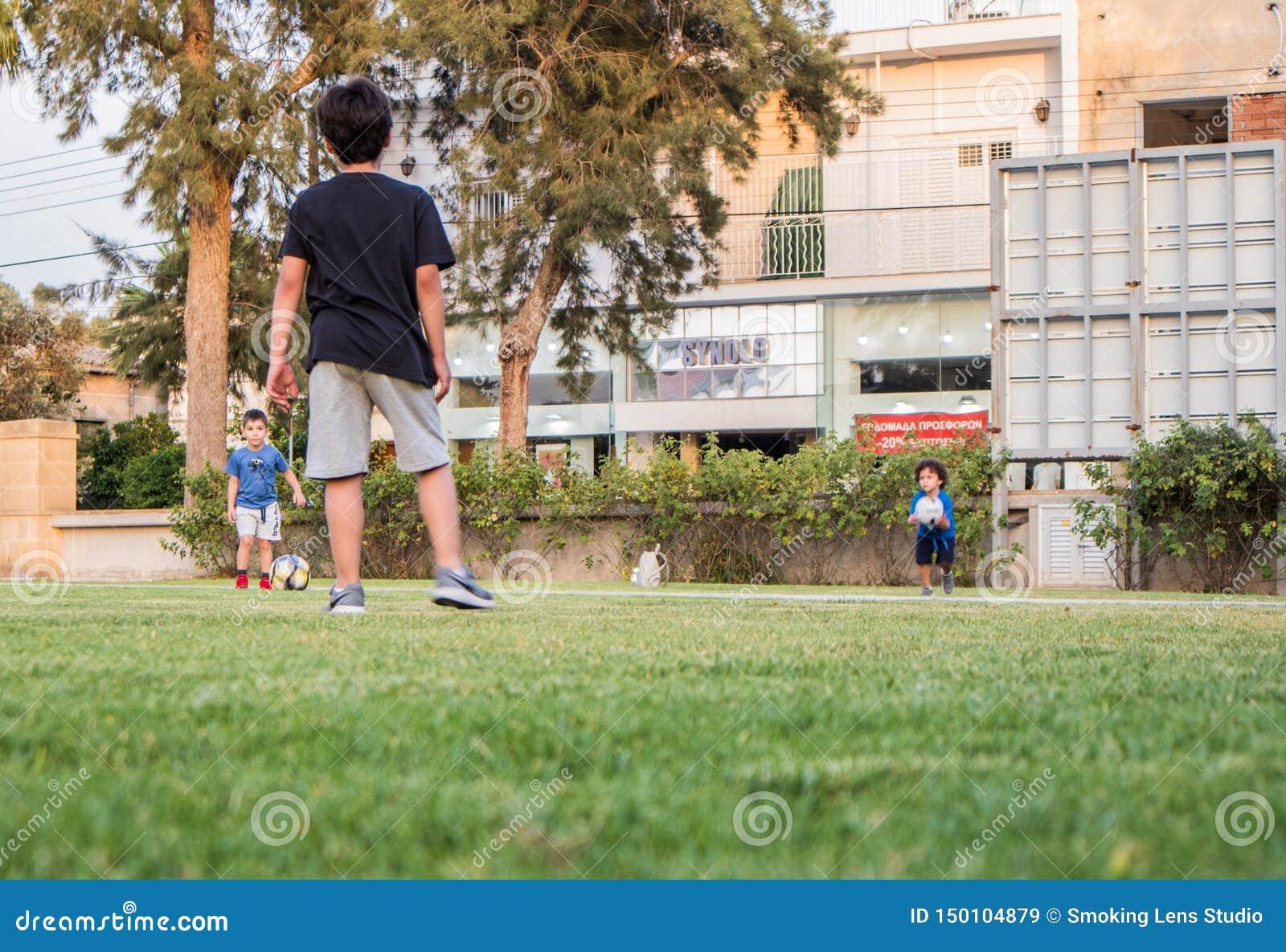 Spela för ungar som är footbal på grönt gräs, i en hem- trädgård