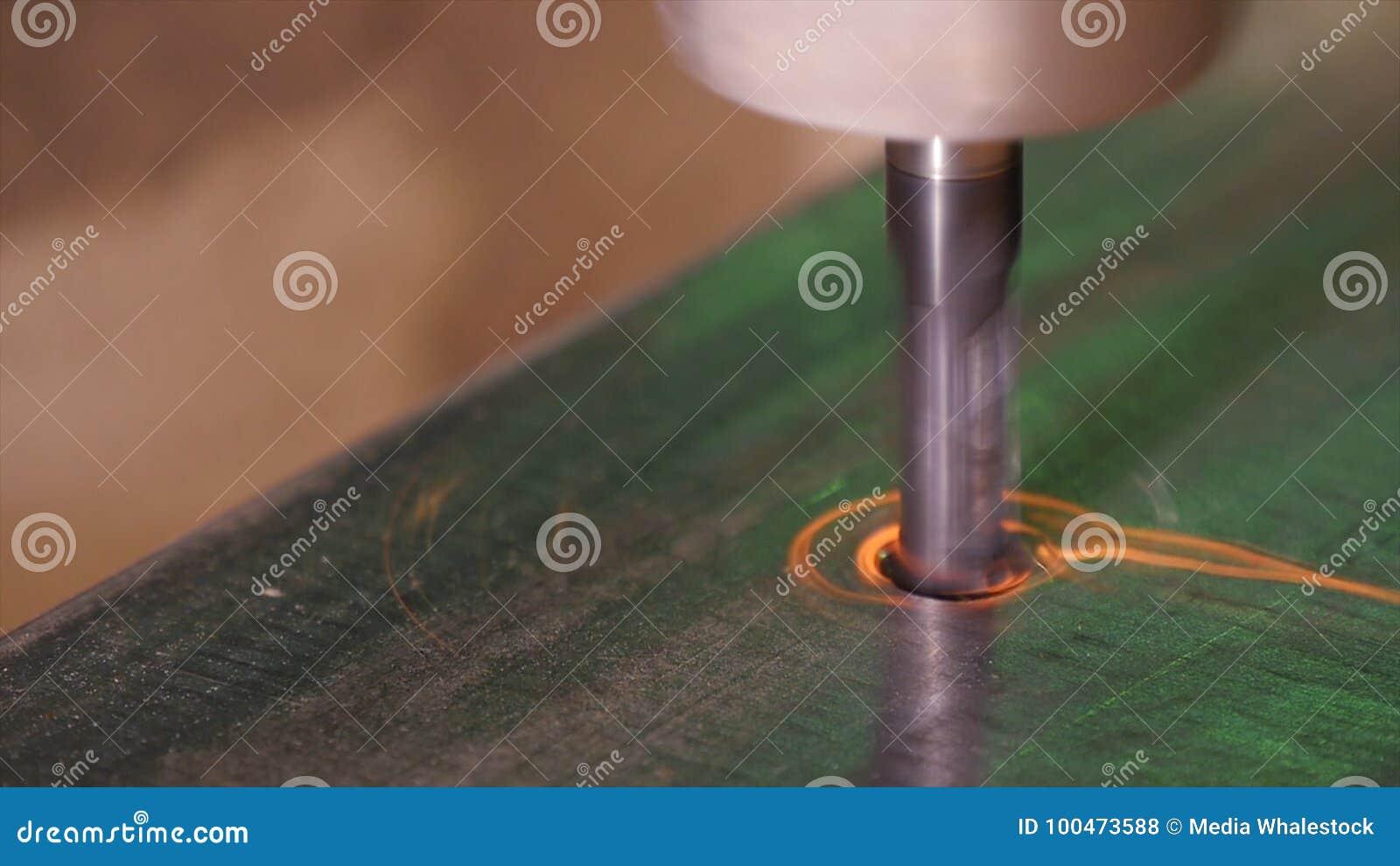 Spela golfboll i hål att borras in i metall Borrandecloseup i metallseminarium Anställd borrar in den plana stålplattan med bänkd