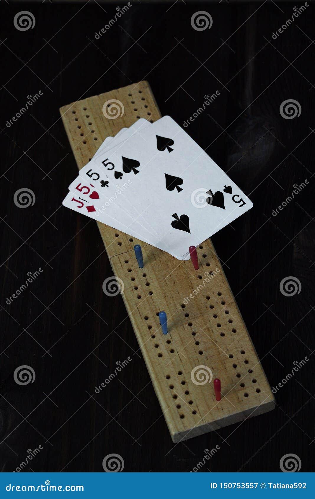 Spela kort och cribbagebräde på svart bakgrund