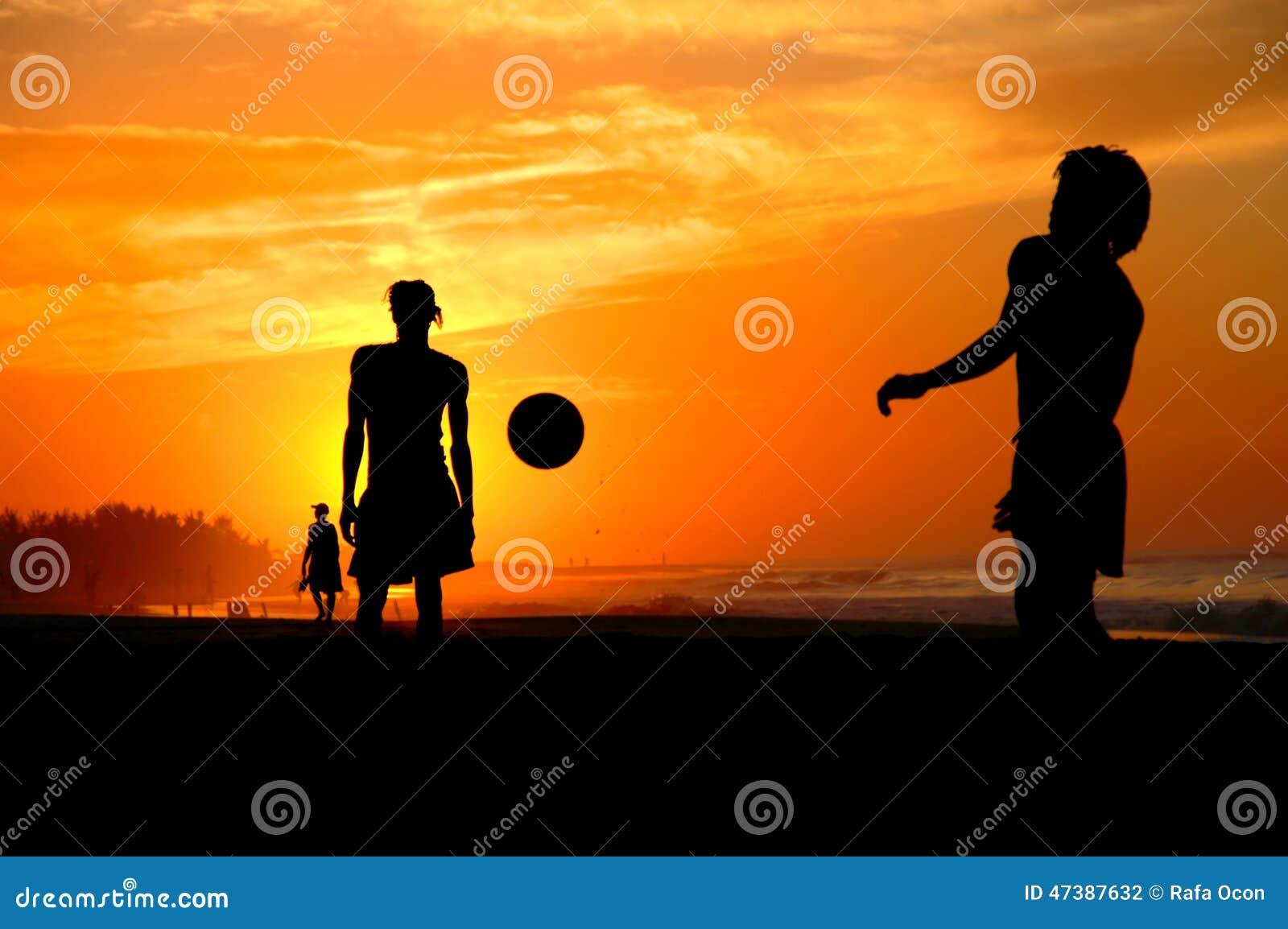 Spela som är footbal på solnedgången på stranden