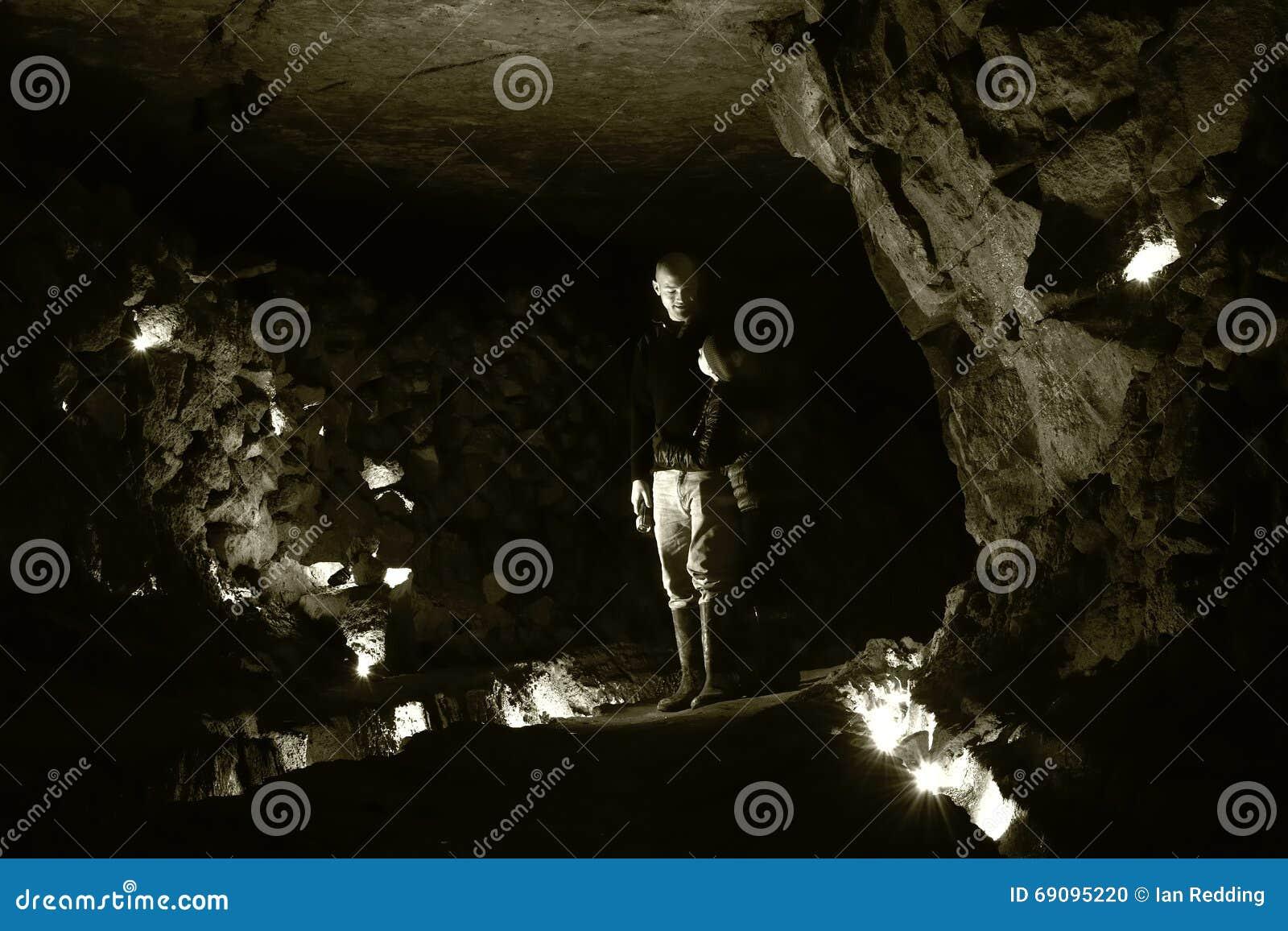 Spelunkers die in kamer in verlaten mijn in Wiltshire, UKMan en kind zich ondergronds in een verlaten mijn bevinden