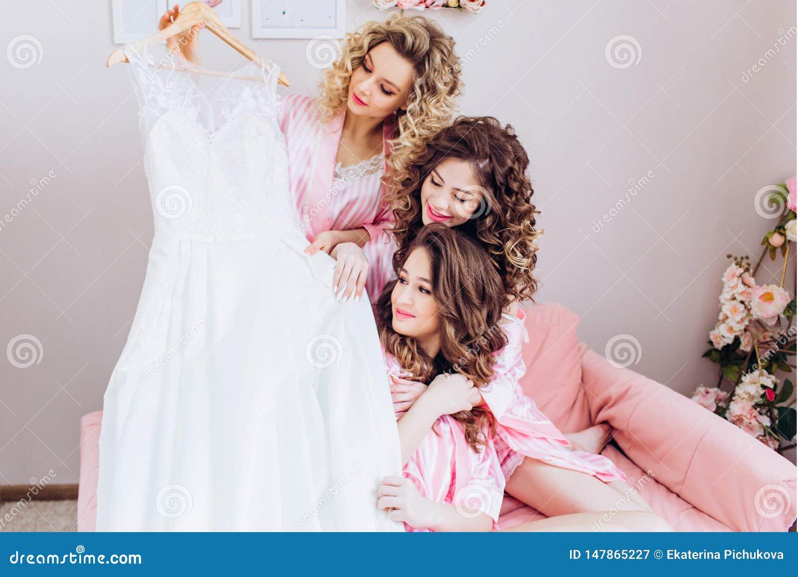 Spensliga tre, unga h?rliga flickor i rosa pyjamas betraktar en br?llopskl?nning