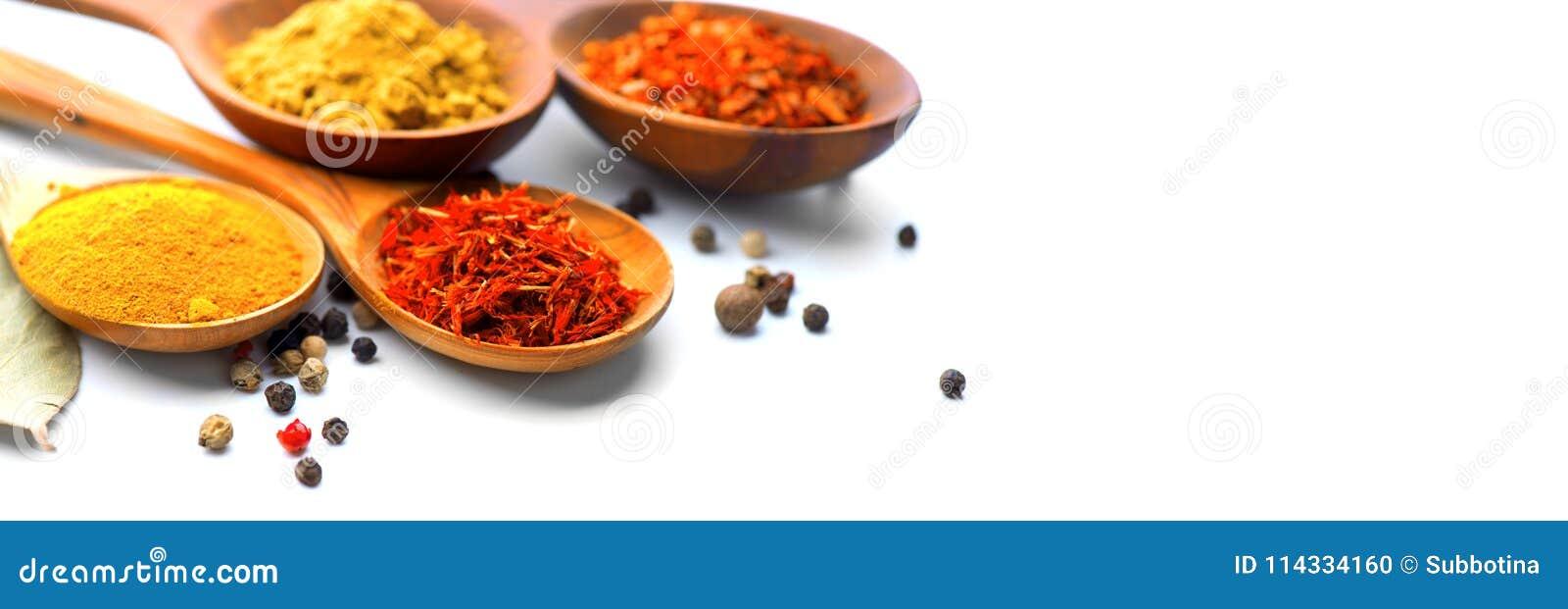 Spezia Varie spezie in cucchiai di legno sopra bianco Curry, zafferano, curcuma, cannella