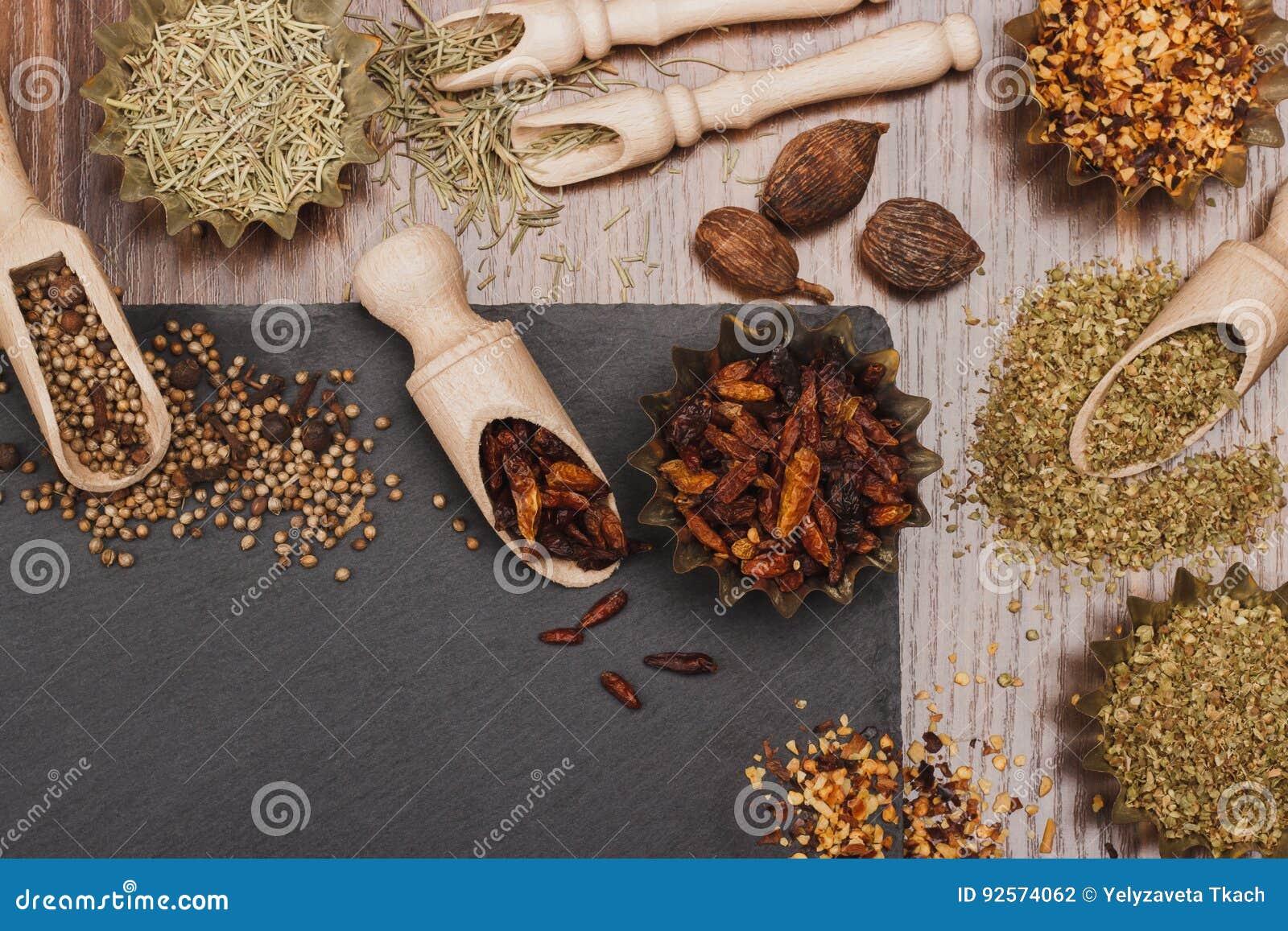 Spezie differenti nel bakeware con i mestoli di legno sullo slone dell ardesia