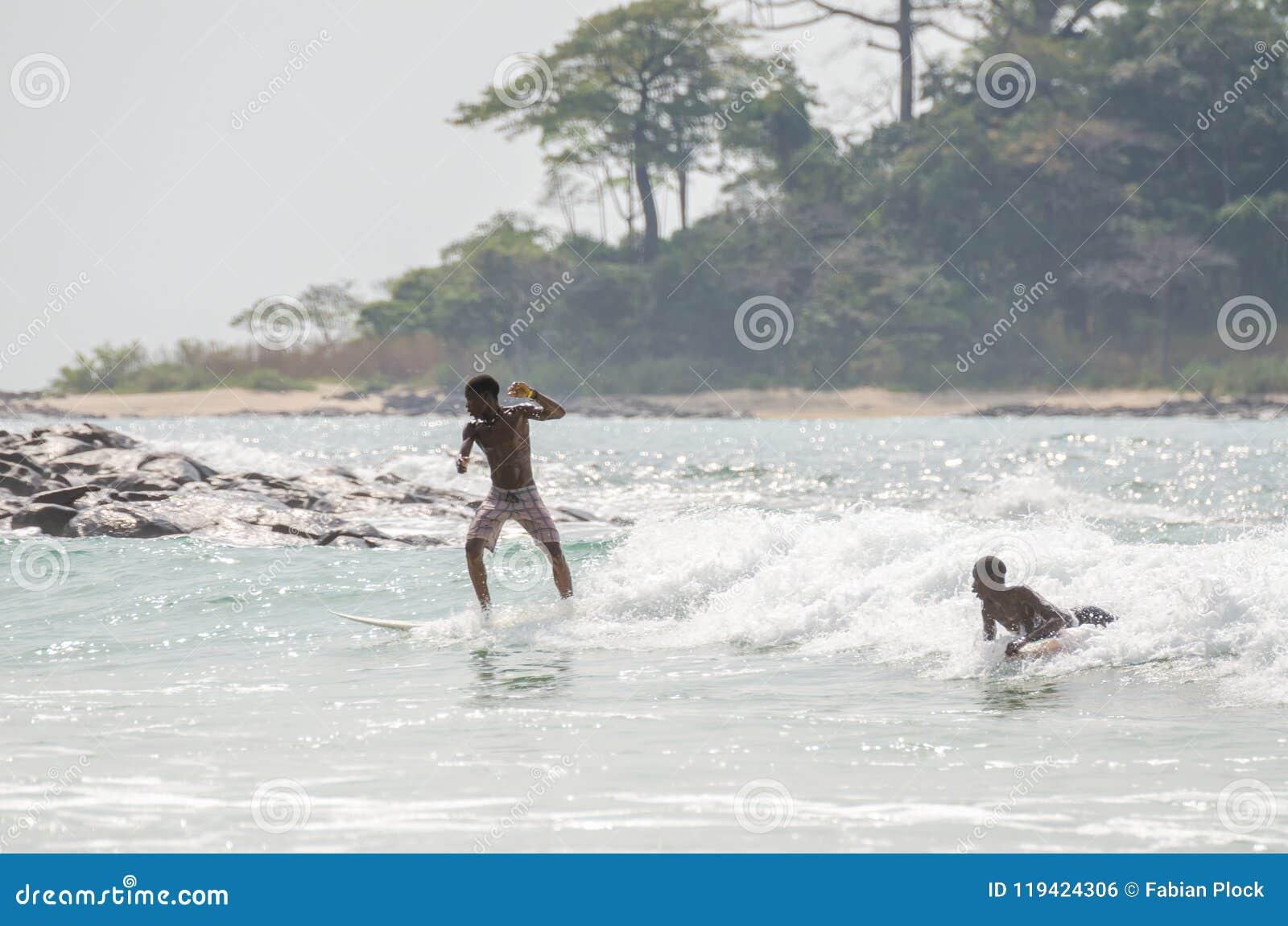 Spiaggia di Bureh, Sierra Leone - 11 gennaio 2014: Due giovani ragazzi africani non identificati che praticano il surfing soltant
