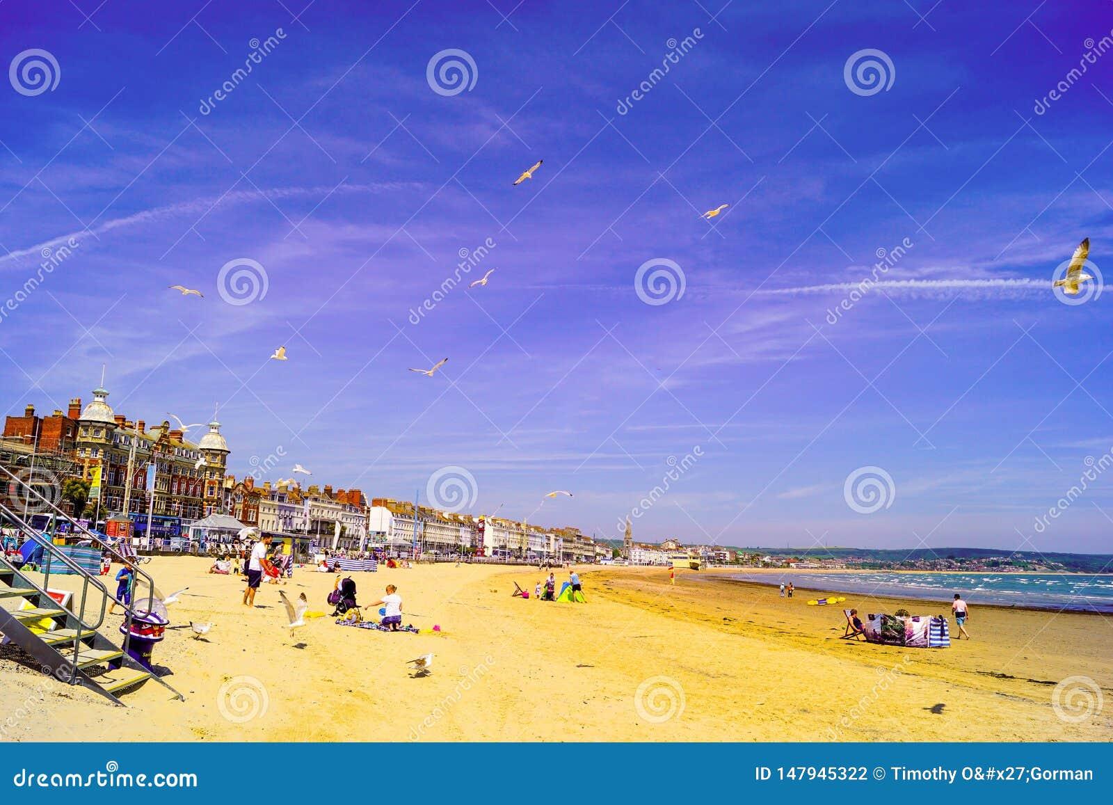 Spiaggia di Weymouth occupata con le famiglie che godono della loro festa