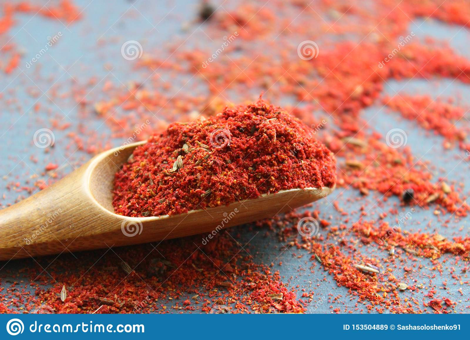 Spices in a wooden spoon. Various Indian spices on black stone table