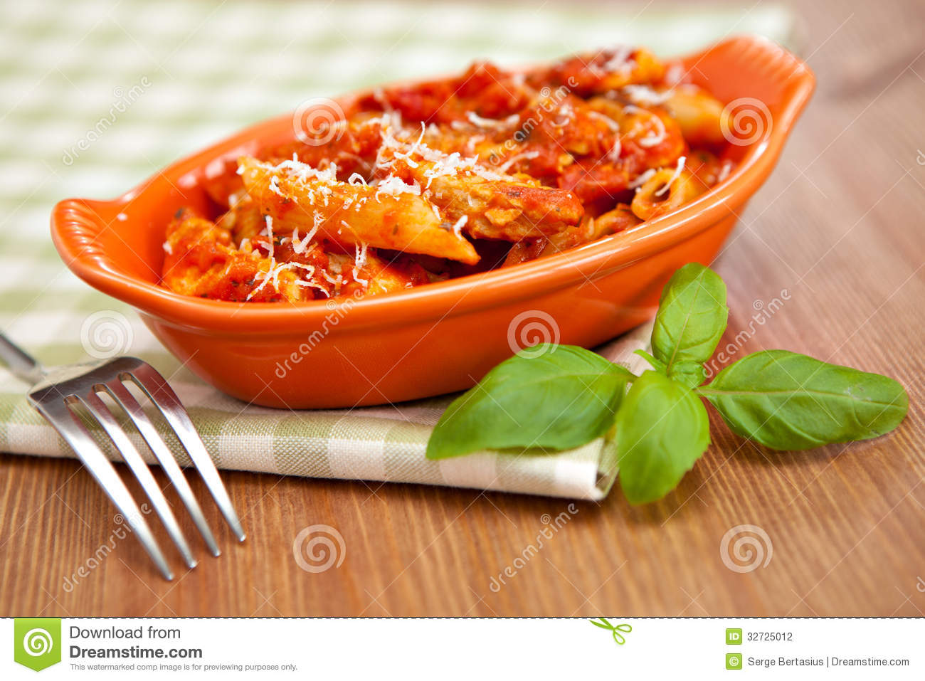 Individual casserole dish with spicy penne pasta on checkered green ...