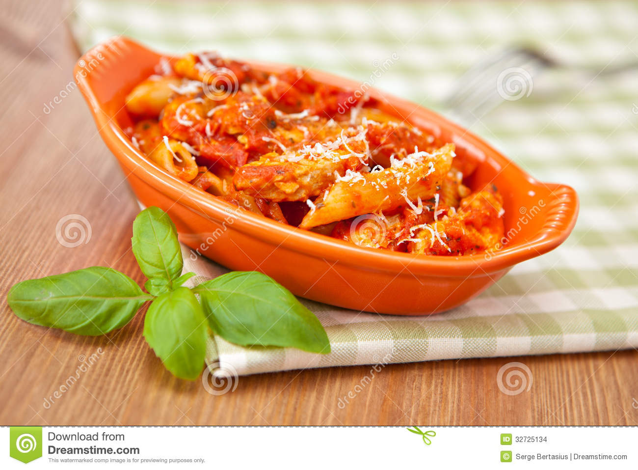 ... casserole dish with spicy penne pasta on checkered green
