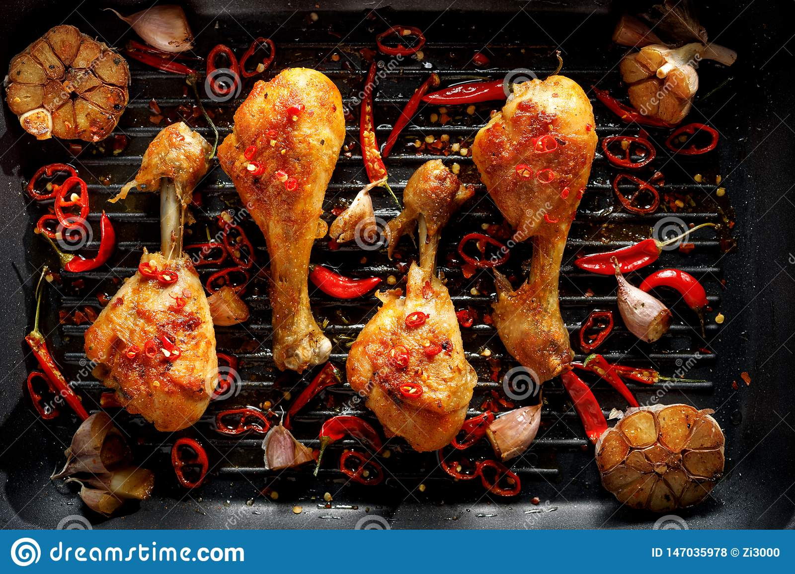 Spicy grilled chicken legs, drumsticks with the addition of chili peppers, garlic and herbs on the grill plate, top view.