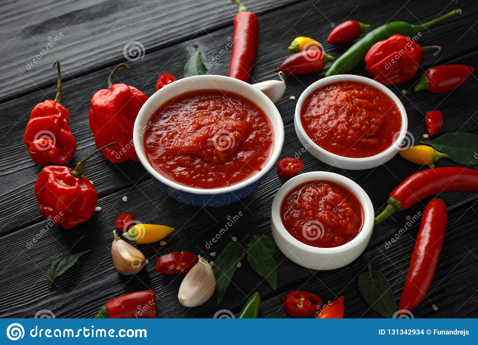 Spicy hot sweet chili sauce with mix of chilli pepper, garlic and tomatoes on rustic wooden background