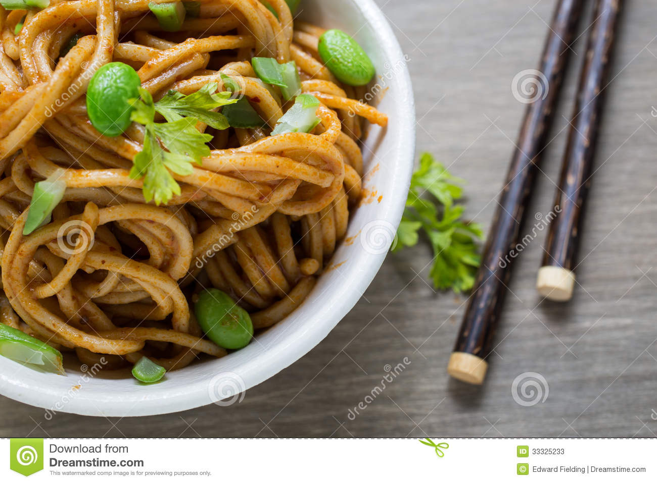 spicy Asian noodles meal with chopsticks.