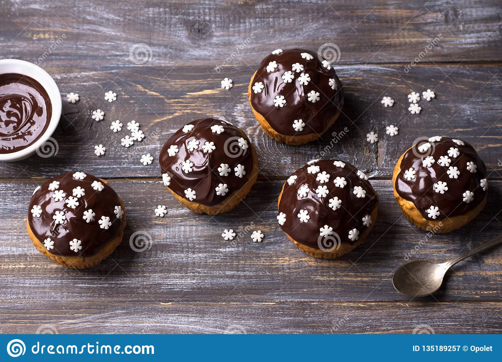 Spicy pumpkin muffins with nuts, decorated with chocolate glaze and sugar snowflakes under the Christmas tree on a wooden table