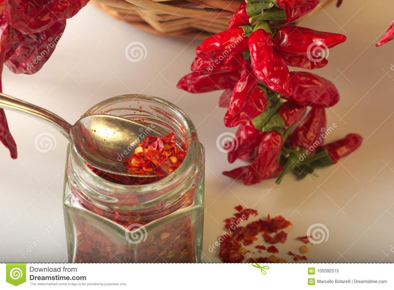 Spicy red pepper ground in the glass jar, with healthy dried peppers in the basket
