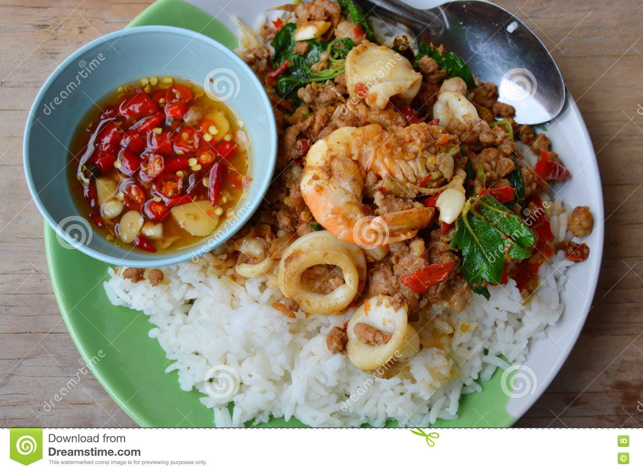 Spicy stir-fried mixed seafood and minced pork with basil leaf on rice