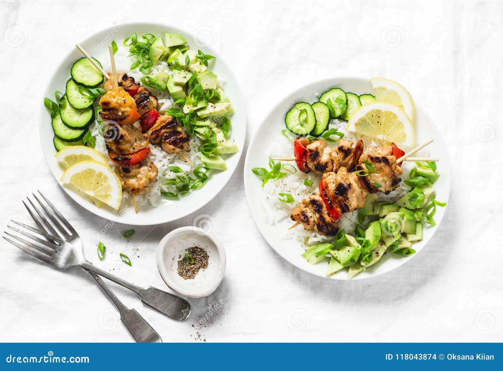 Spiedi arrostiti del pollo della calce del miele del peperoncino rosso con la salsa dell avocado e del riso su fondo leggero, vis