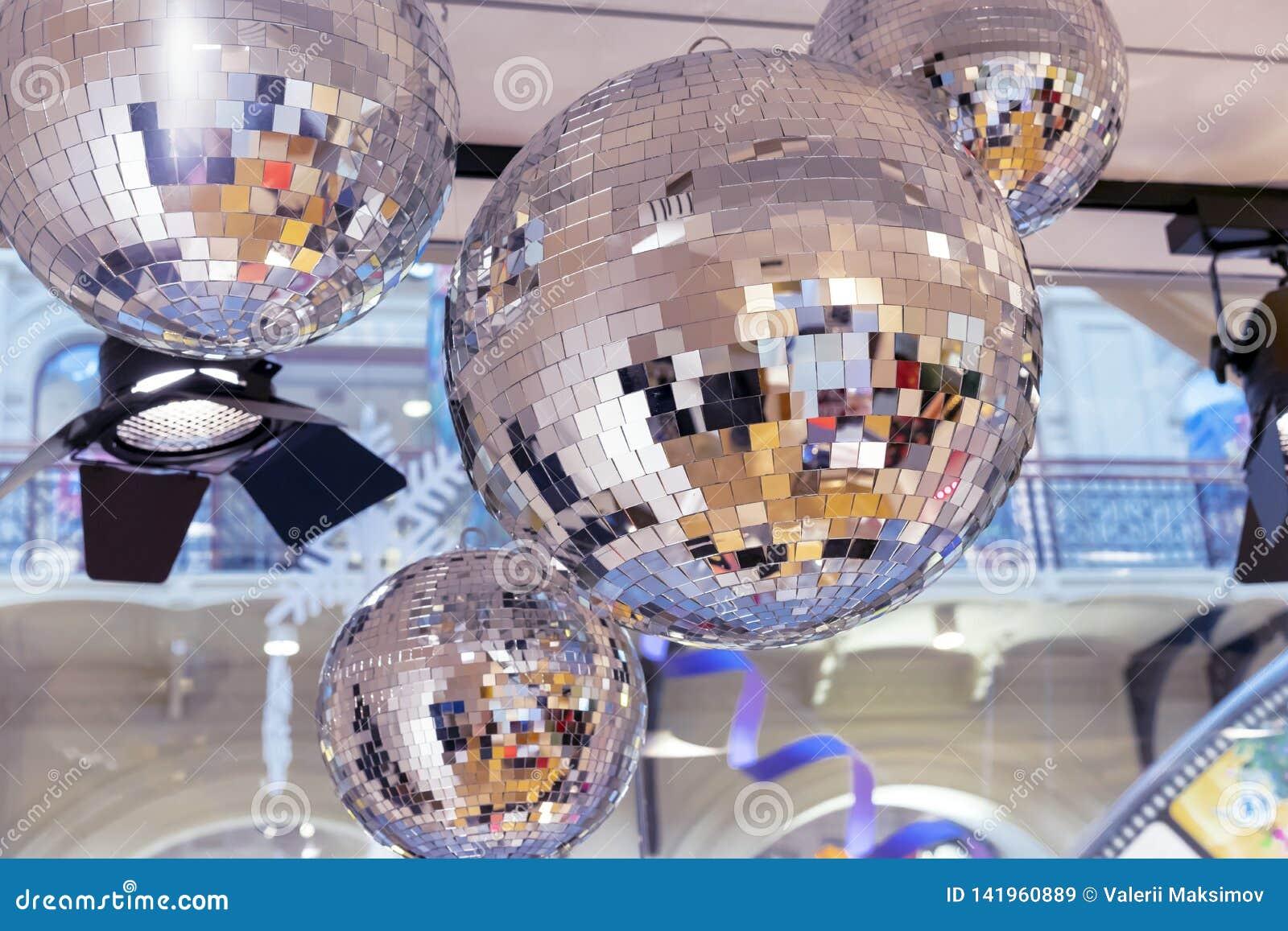 Spiegeldiscobälle und ein Scheinwerfer auf einem Hintergrund des neuen Jahres