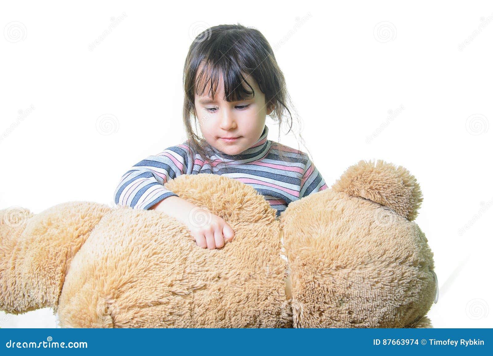 Spielwaren- und Leutekonzept - nettes kleines Mädchen, das Teddybären umarmt
