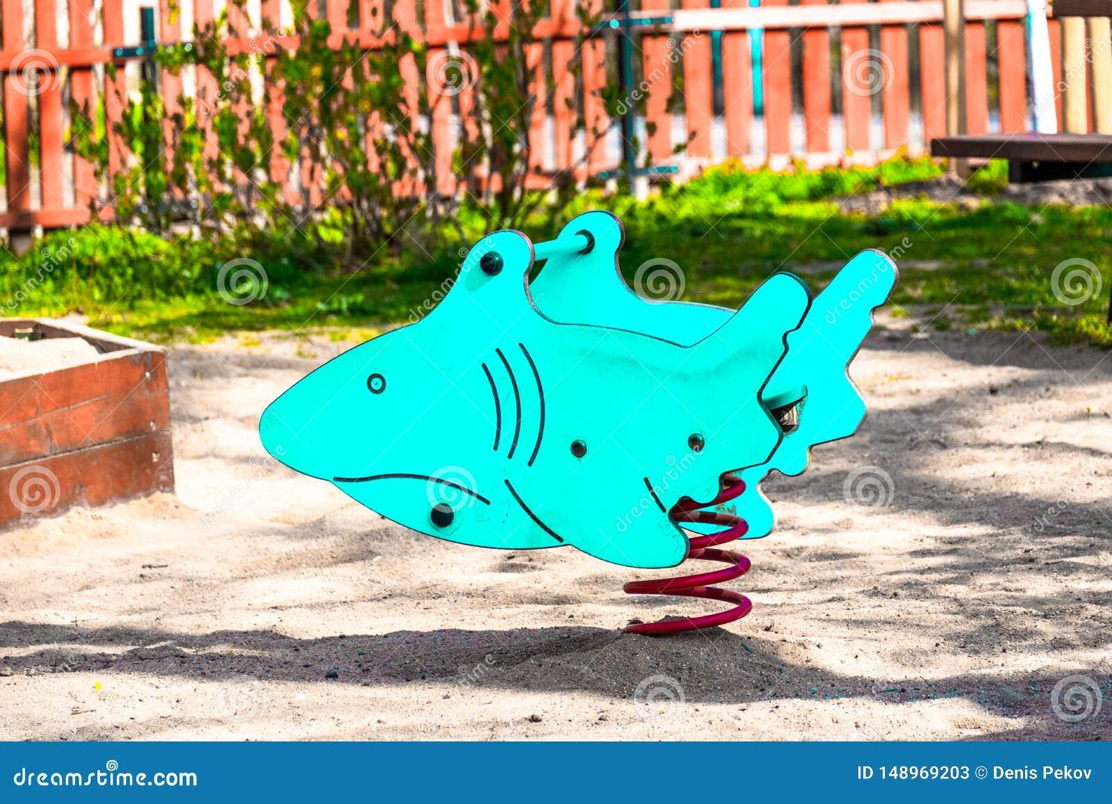 Spielzeughaifisch der Kinder, blaue Farbe, auf dem Spielplatz für Kinder