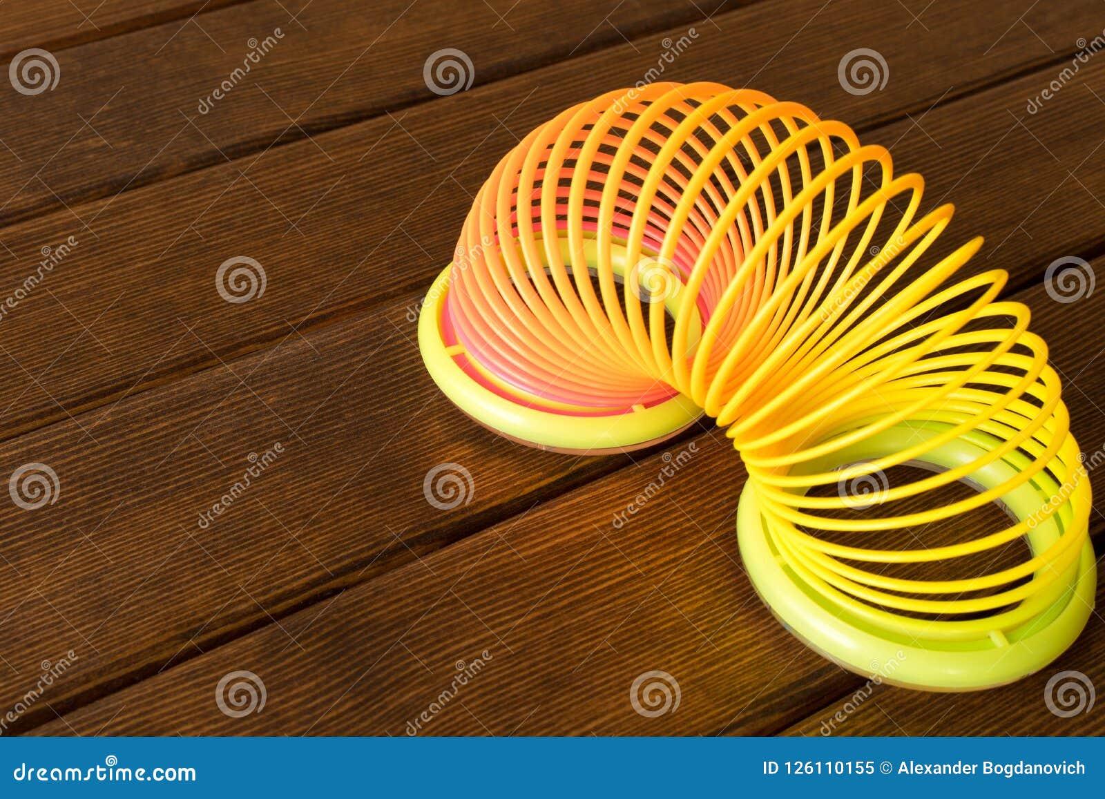 Spielzeugplastikregenbogen auf einem Holztisch Mehrfarbige Spirale für