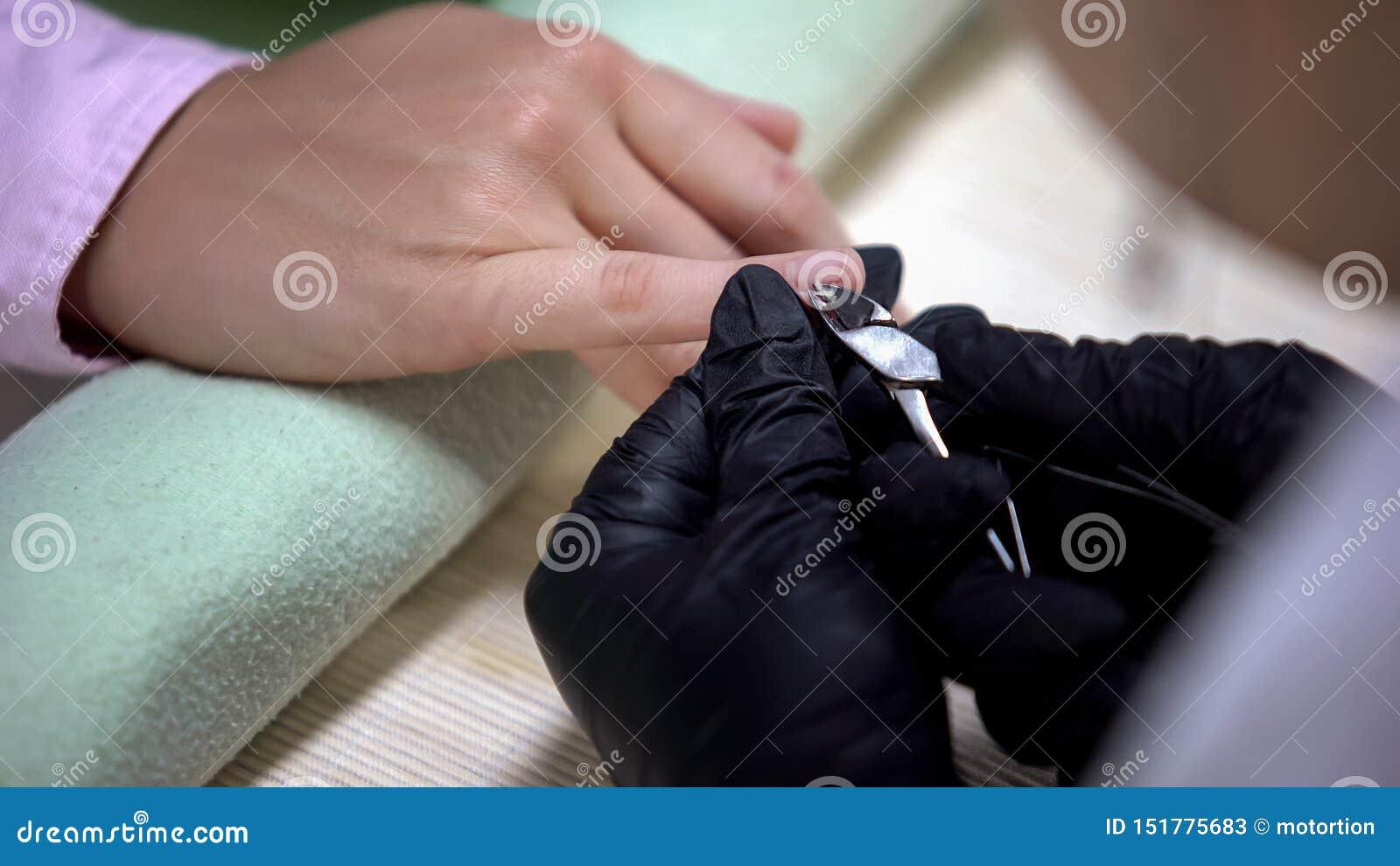 Spijkermeester die in handschoenen opperhuid met tang, hygiëne in schoonheidssalon verwijderen