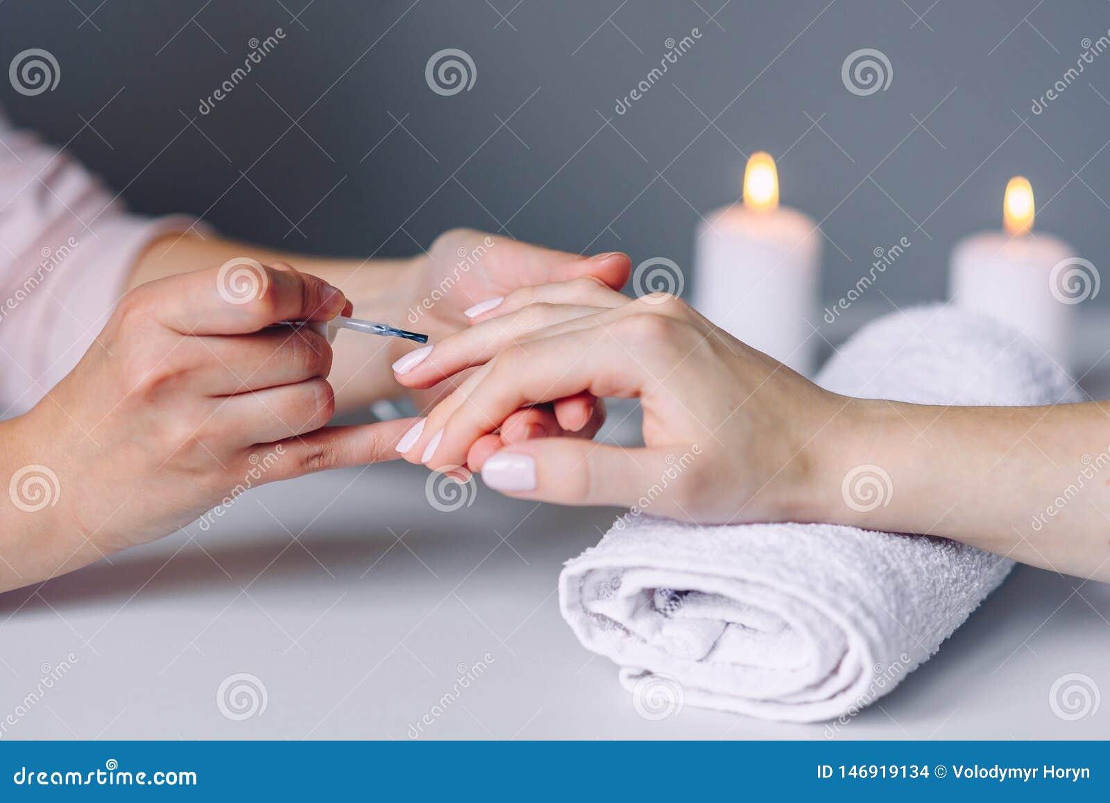 Spika omsorg och manikyr Spikar den sunda naturliga kvinnan f?r closeupen i sk?nhetsalong Manikyristen som handen m?lar klienten,
