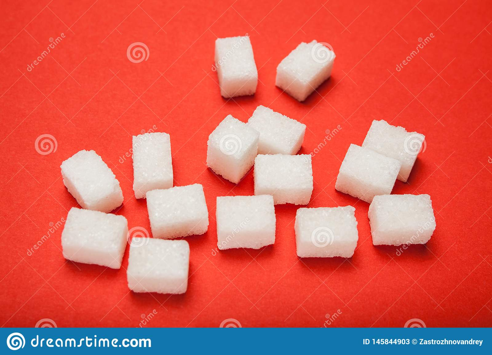 Spilled cubes of sugar on a red background
