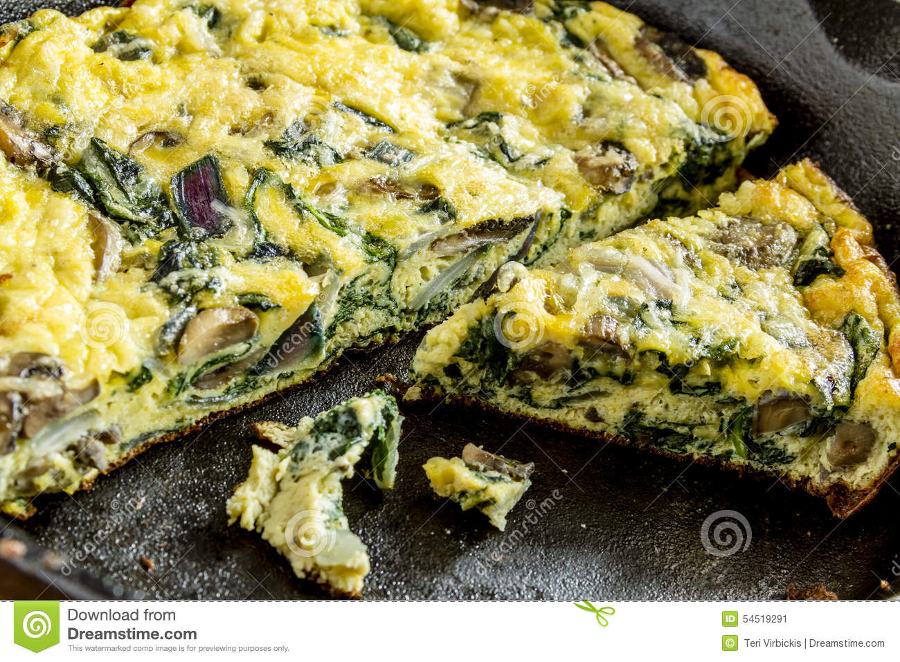 Close up of a spinach mushroom and purple onion frittata in a cast ...