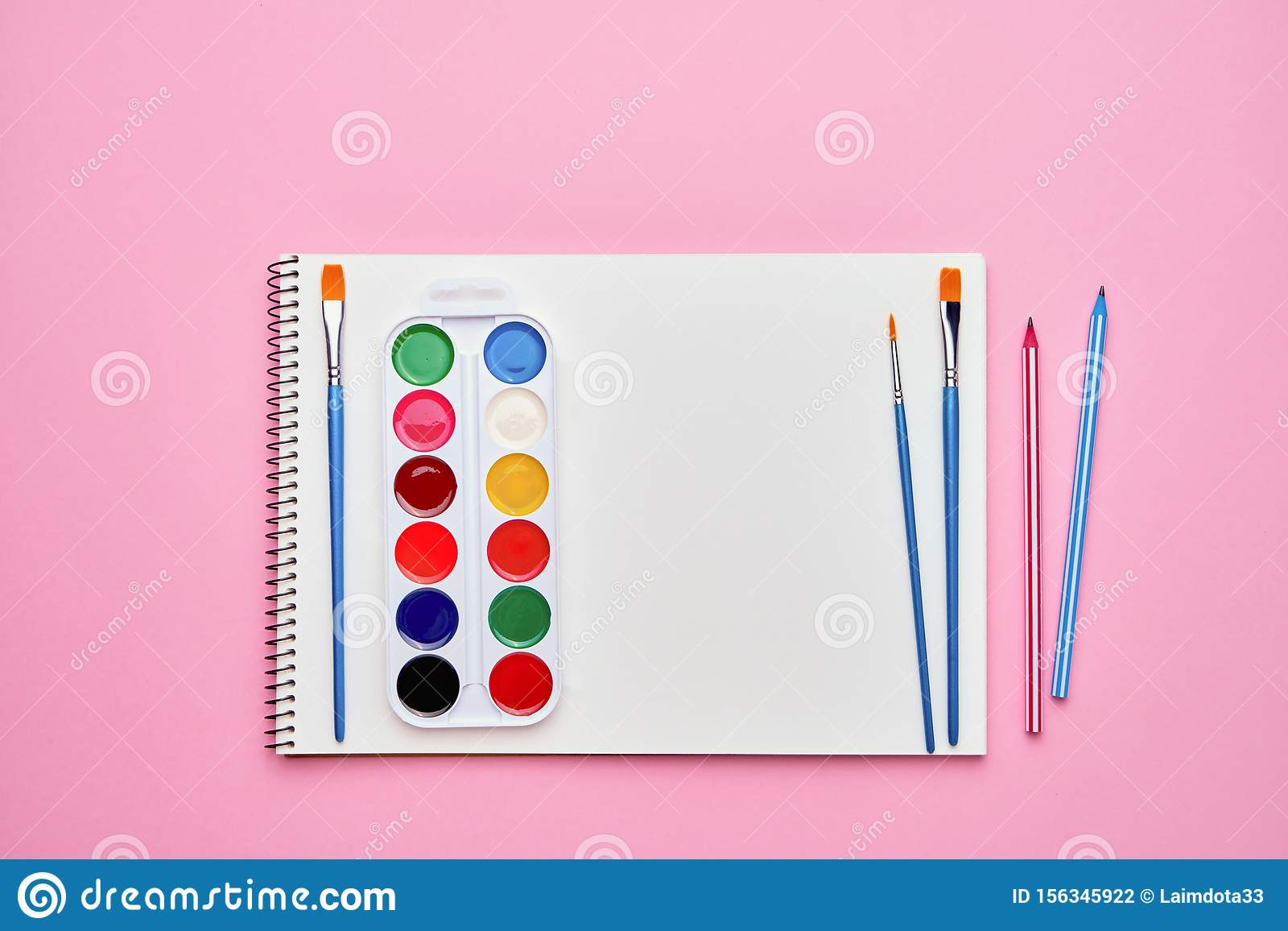 Spiral notepad with pencils. Notebook on pastel pink backdrop. Back to school concept. Copy space, top view