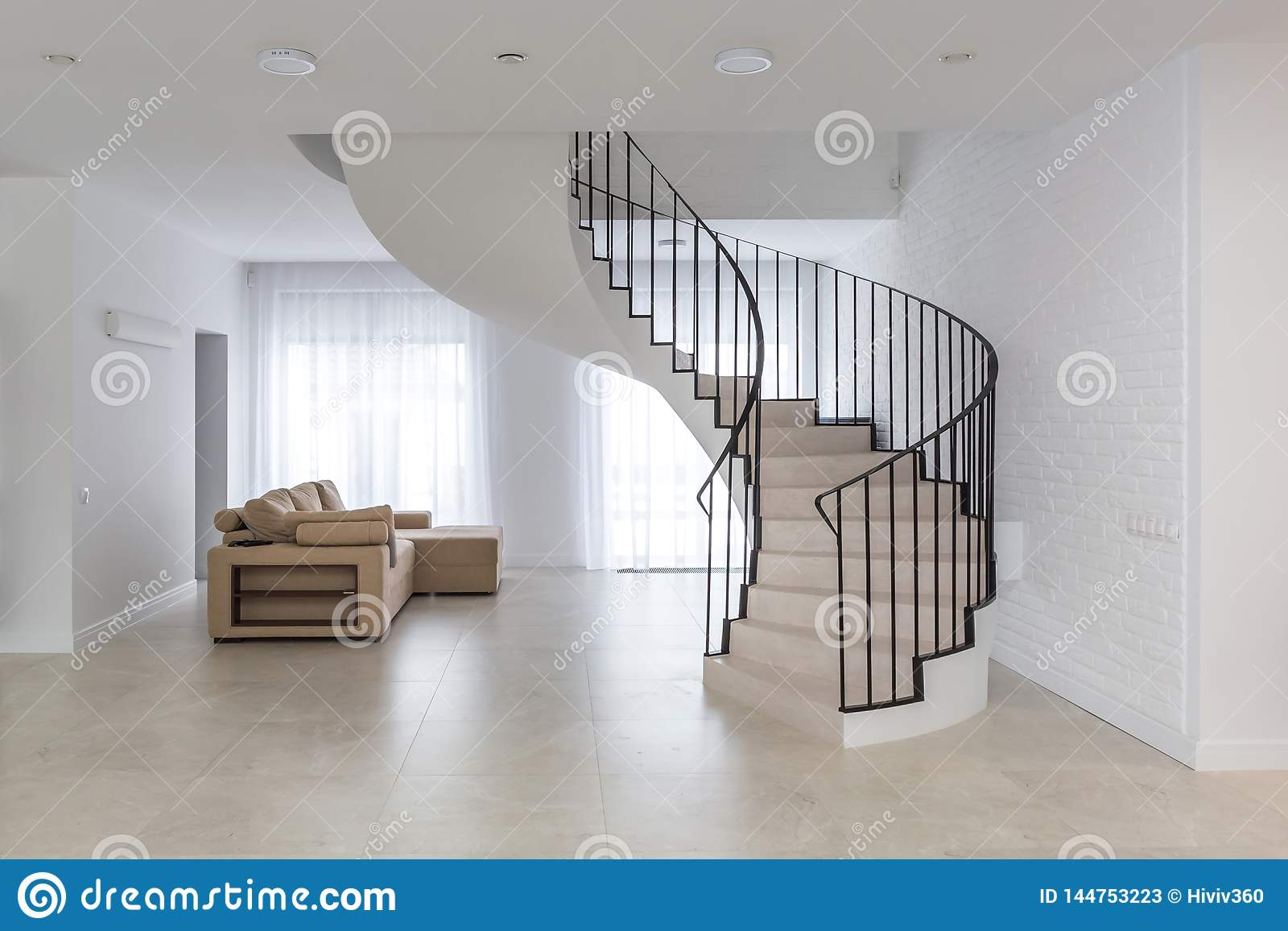 Spiral staircase in bright interior with white brick wall in elite expensive
