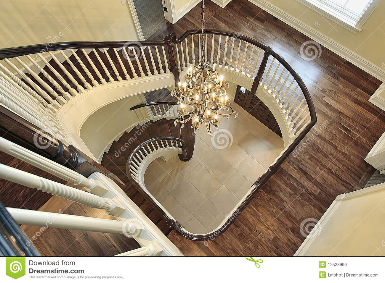 Spiral staircase with foyer view in new luxury construction home.