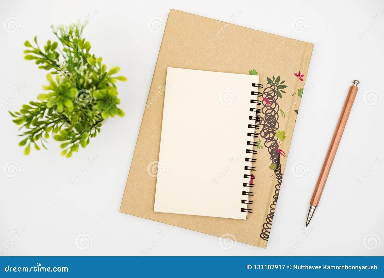 Spitzenansichtnotizbuch mit Farbbleistift auf weißer Tabelle