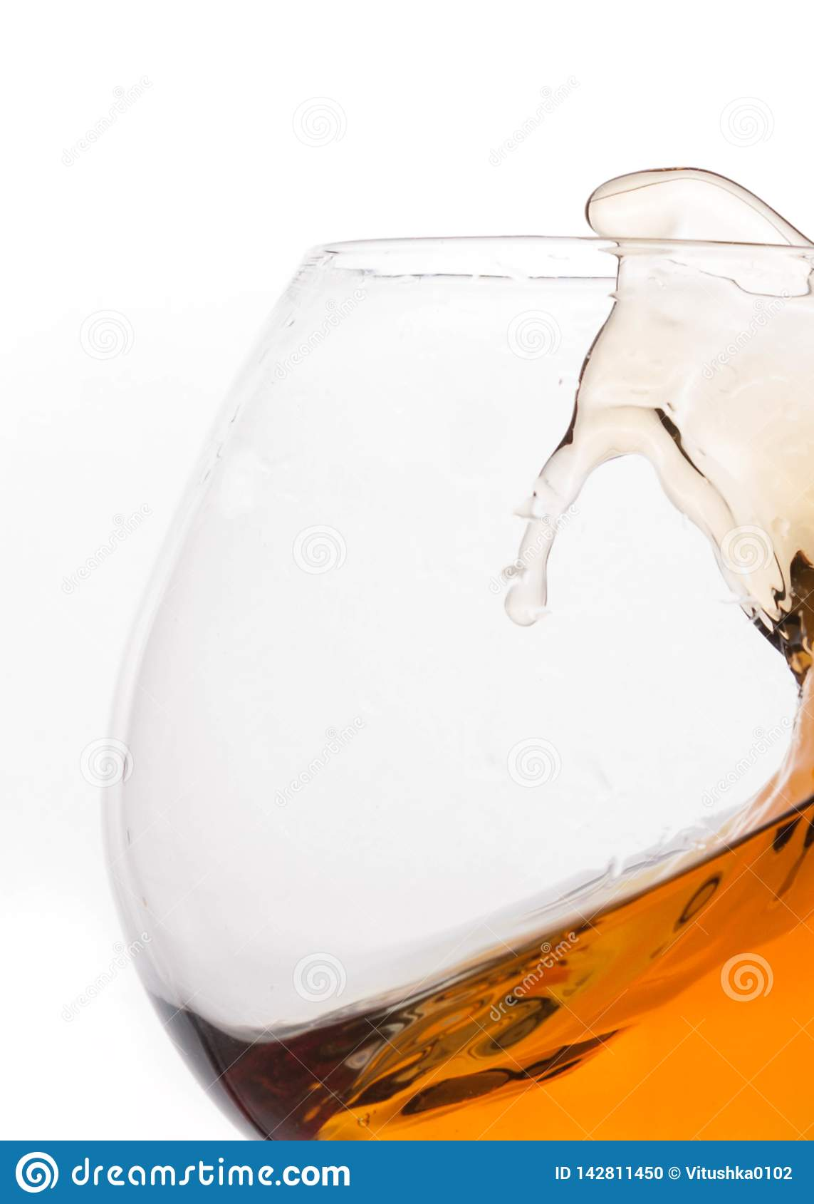 Splash of brown whiskey in transparent glass with reflection