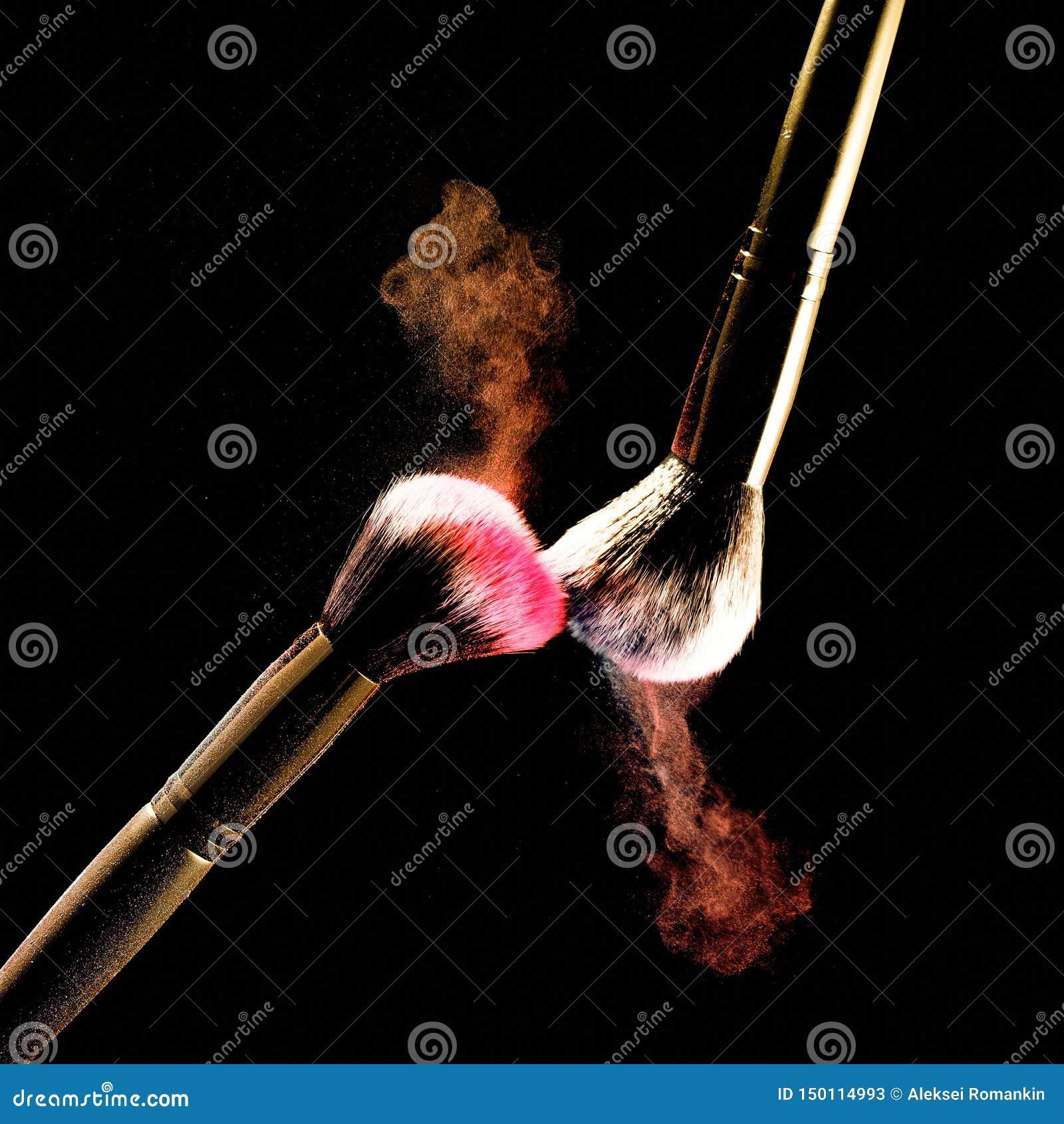 Splash of powder on a black background brushes for make up on a black background