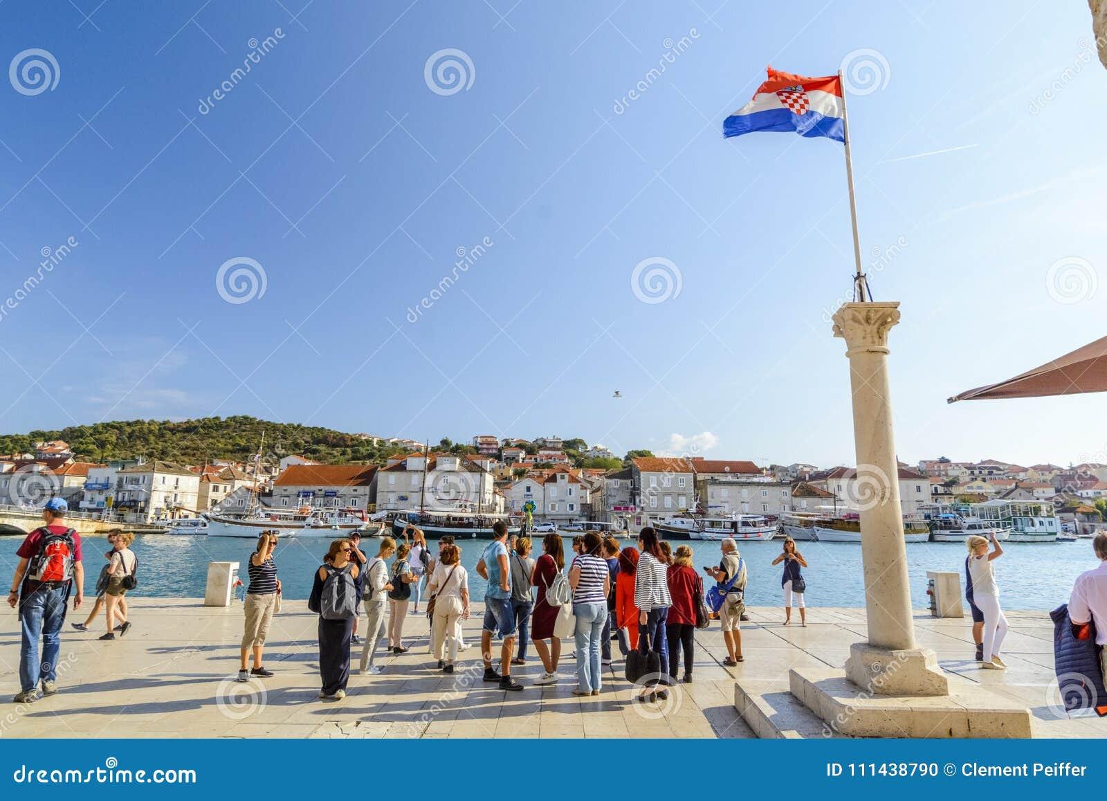 SPLITTRING KROATIEN, OKTOBER 01, 2017: turist som går på stranden och tar bilden av den kluvna marina nära den kroatiska flaggan