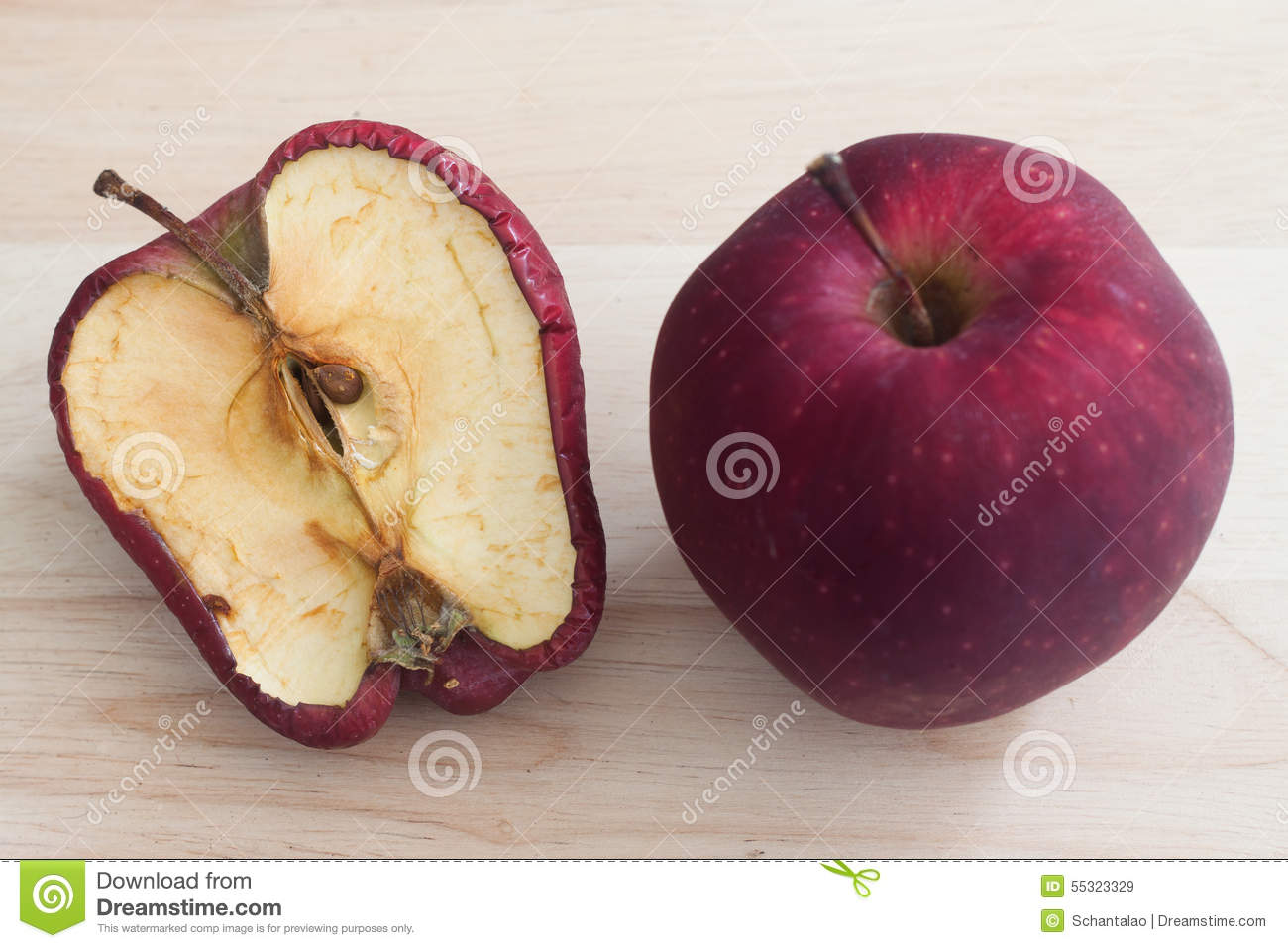 spoiled one bad red apple on wooden background Healthy and rotten apples