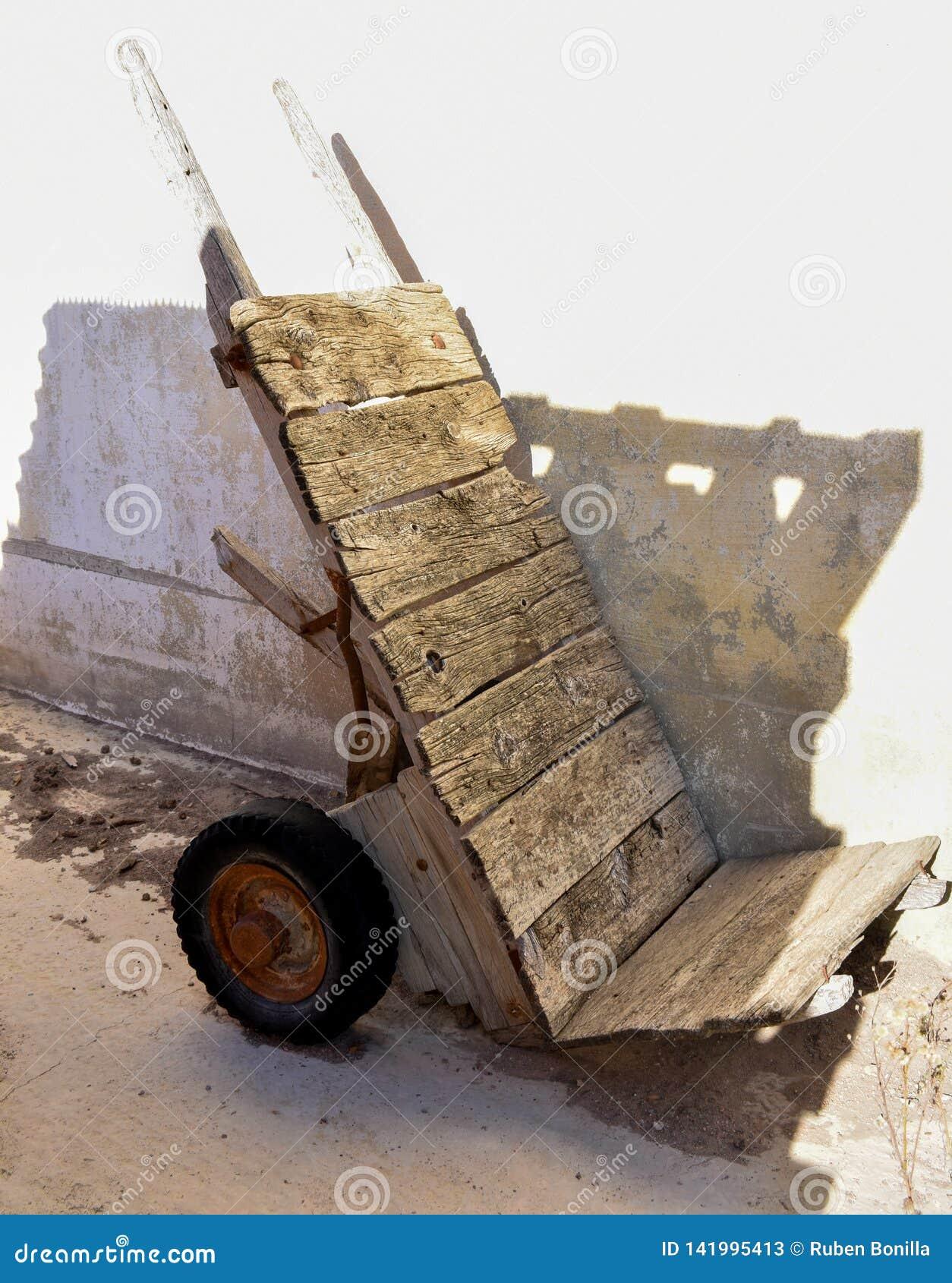 Spoilted houten zeer oud karretje en verliet bij een hoek van een tuin De wielen van het karretje zijn unusefull en roestig
