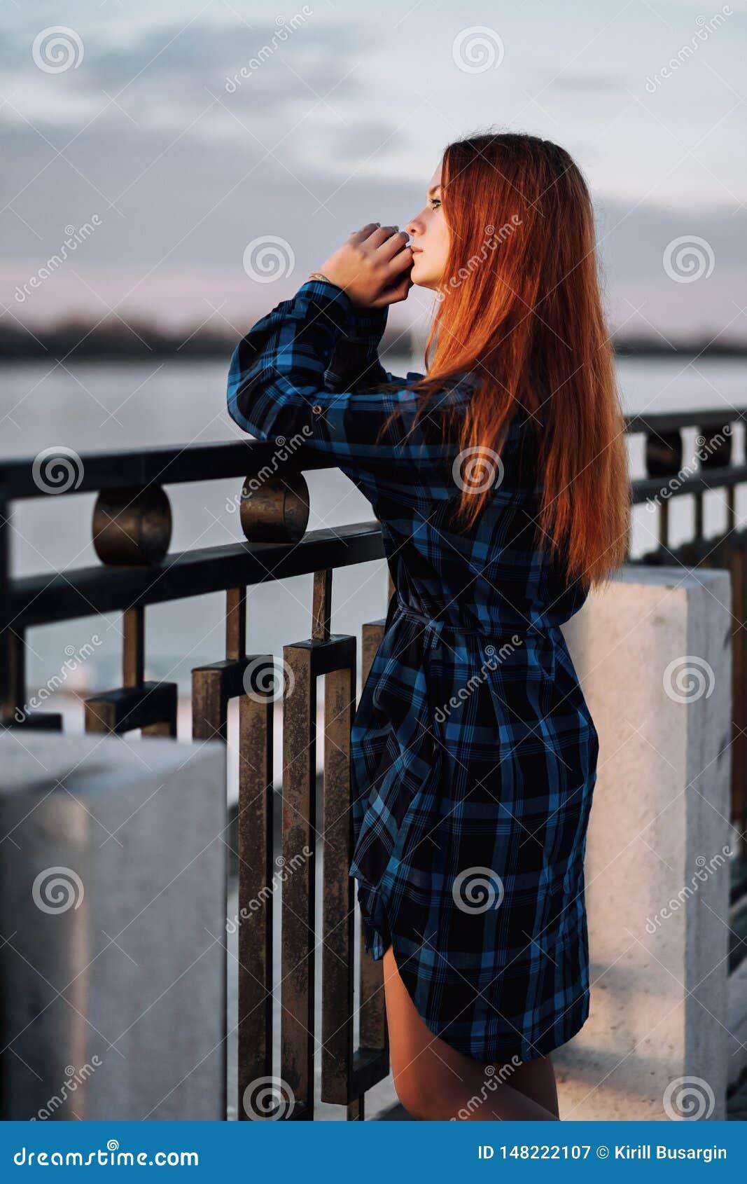 Spokojna dziewczyna stoi samotnie na nabrze?u przed ogrodzeniem bulwar