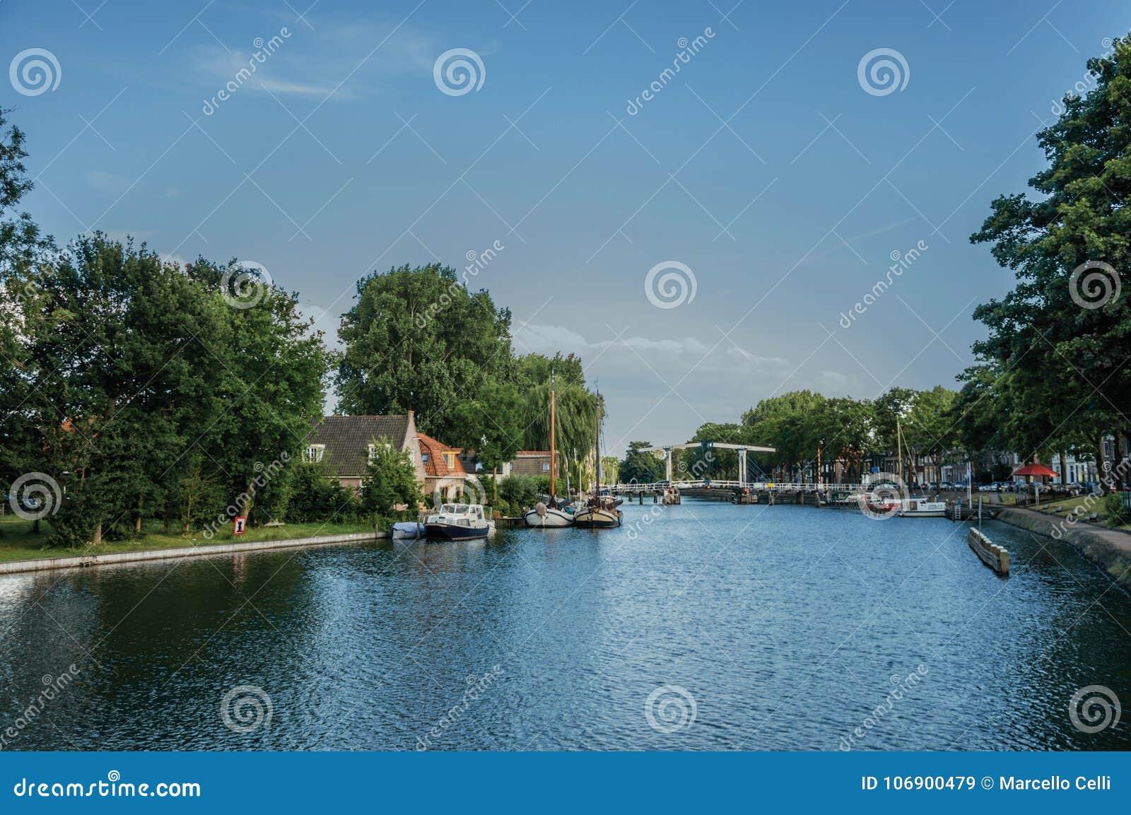 Spokojna rzeka z gajem i mostem, łodzie cumował w molu ceglani domy i pogodnym niebieskim niebie w Weesp